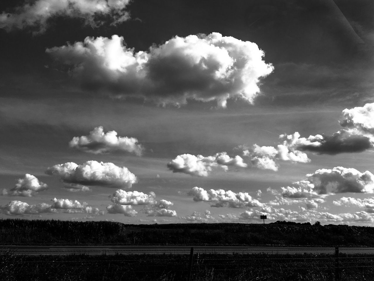 Empty Road And Field Against Cloudy Sky