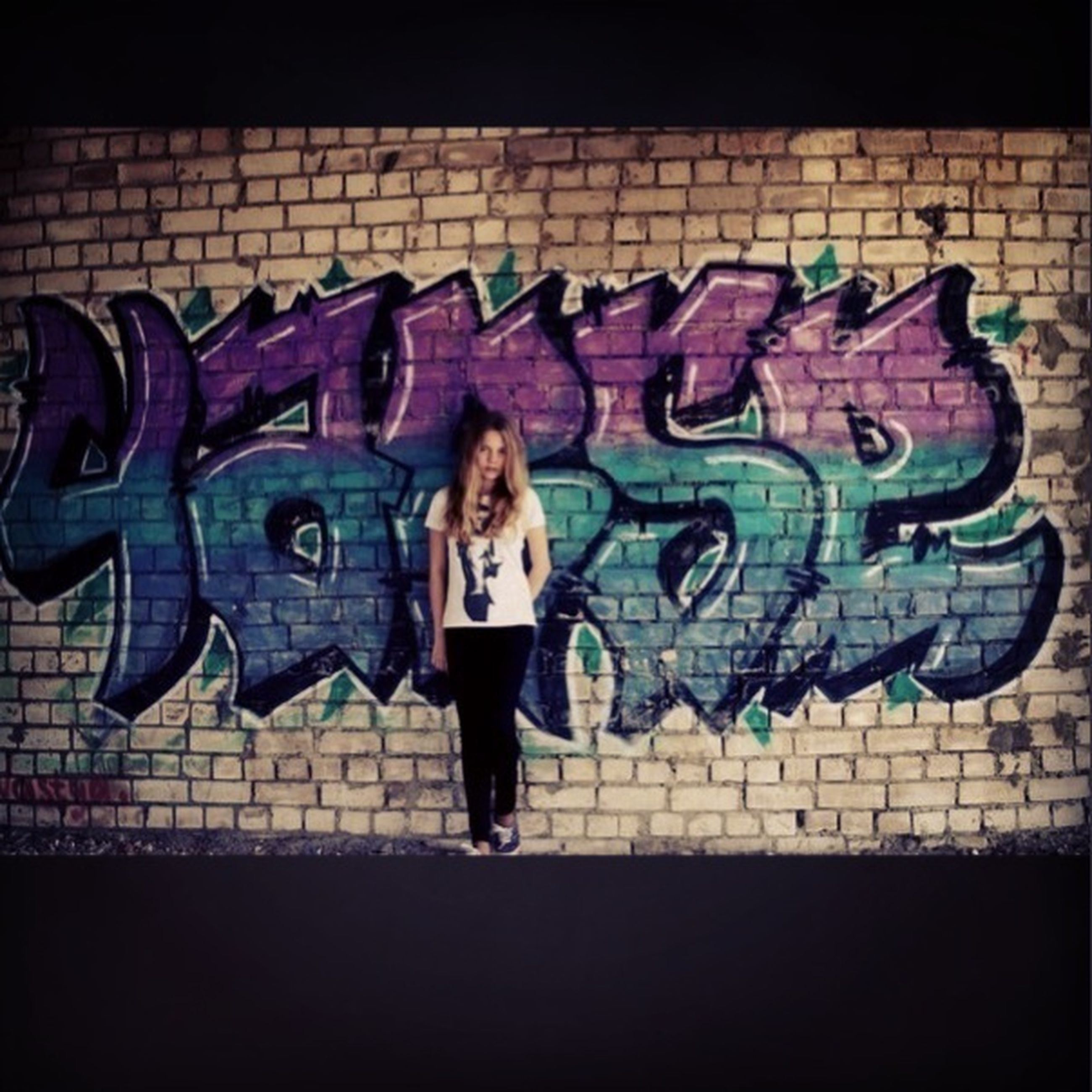 full length, standing, graffiti, wall - building feature, lifestyles, casual clothing, art, leisure activity, brick wall, portrait, front view, creativity, built structure, art and craft, looking at camera, architecture, outdoors, person