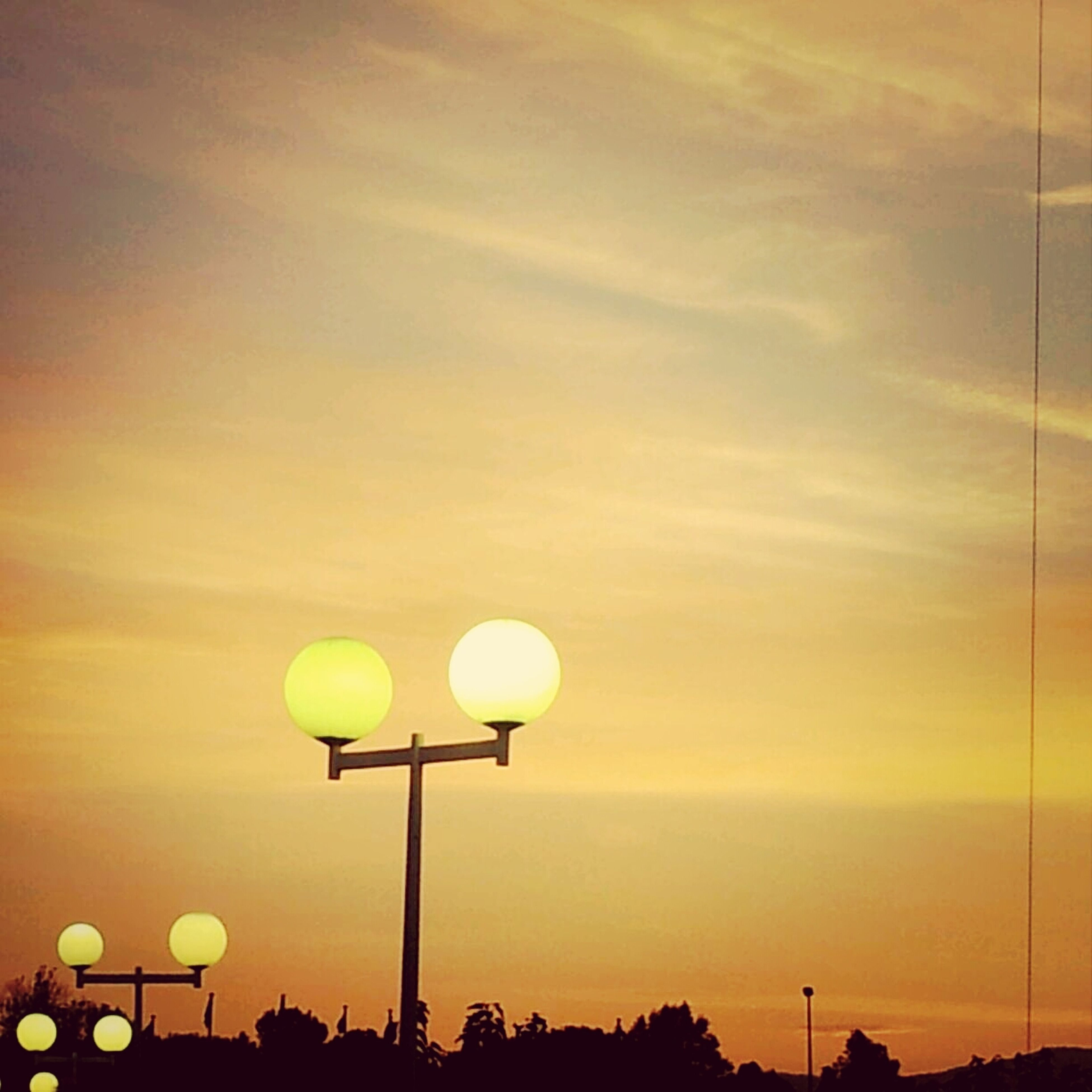 low angle view, street light, lighting equipment, sky, sunset, yellow, electricity, silhouette, orange color, pole, nature, electric light, illuminated, no people, outdoors, beauty in nature, tree, tranquility, cloud - sky, dusk