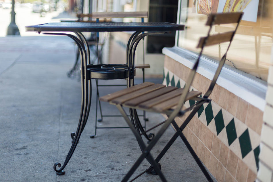 Cafe tables and chairs Black Tables Building Building Exterior Cafe Cafe Entrance Chair Close-up Day Empty Entrance Focus On Foreground Glow Metal Tables No People Outdoors Patio Reflection Reflective Seat Shade Shaded Shallow Depth Of Field Street Table Windows