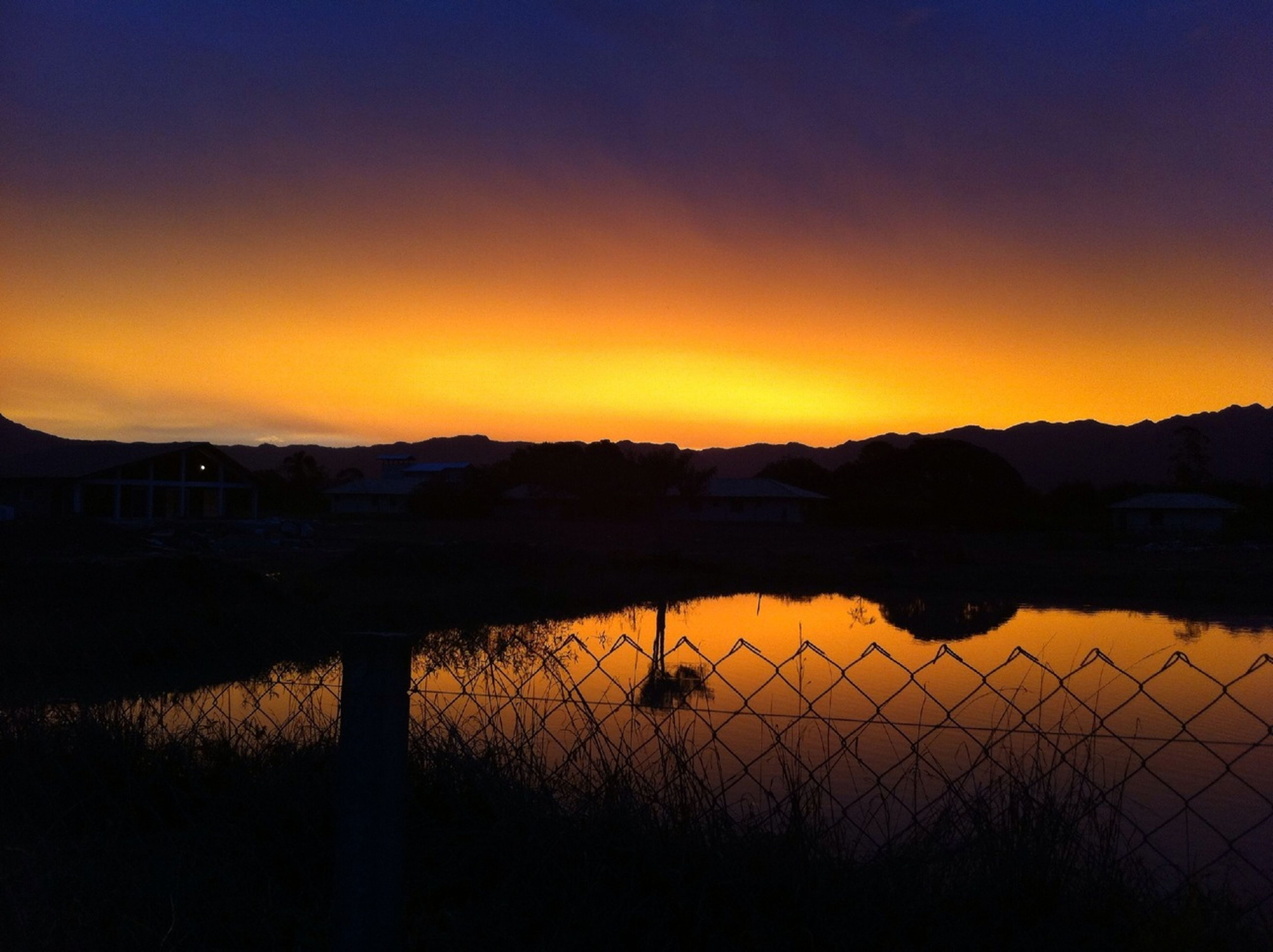 sunset, tranquil scene, tranquility, orange color, scenics, mountain, landscape, beauty in nature, sky, fence, silhouette, idyllic, nature, mountain range, dusk, field, railing, water, no people, outdoors