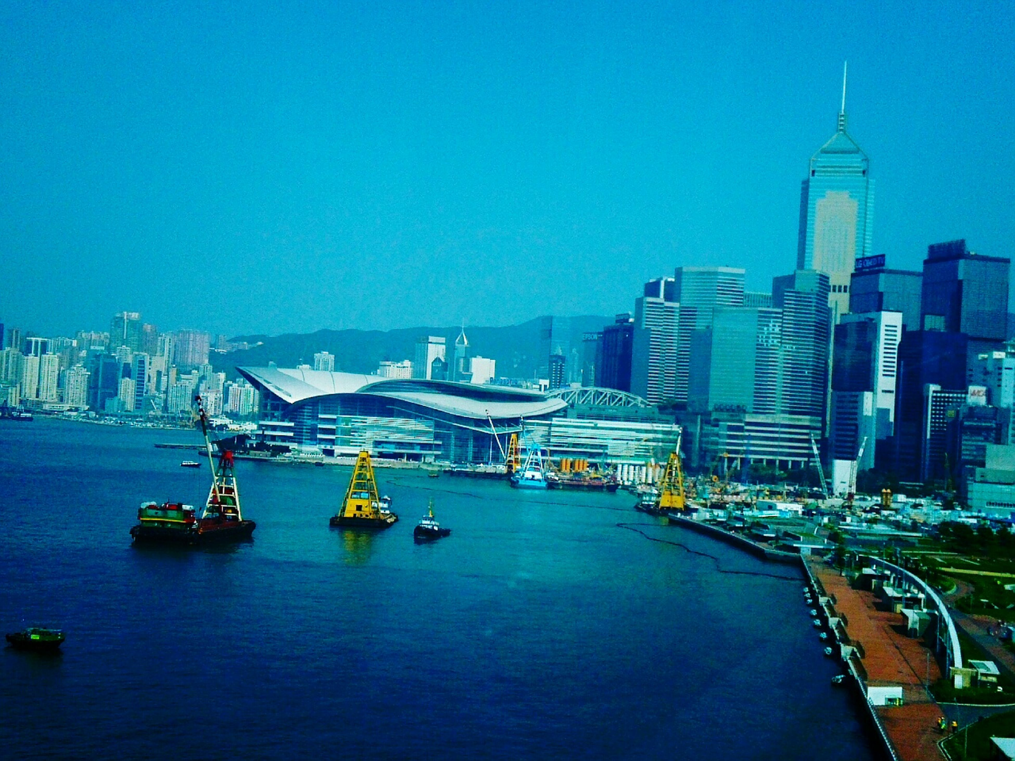 architecture, building exterior, built structure, city, water, cityscape, tower, clear sky, transportation, copy space, waterfront, skyscraper, tall - high, blue, river, nautical vessel, capital cities, travel destinations, travel, sea