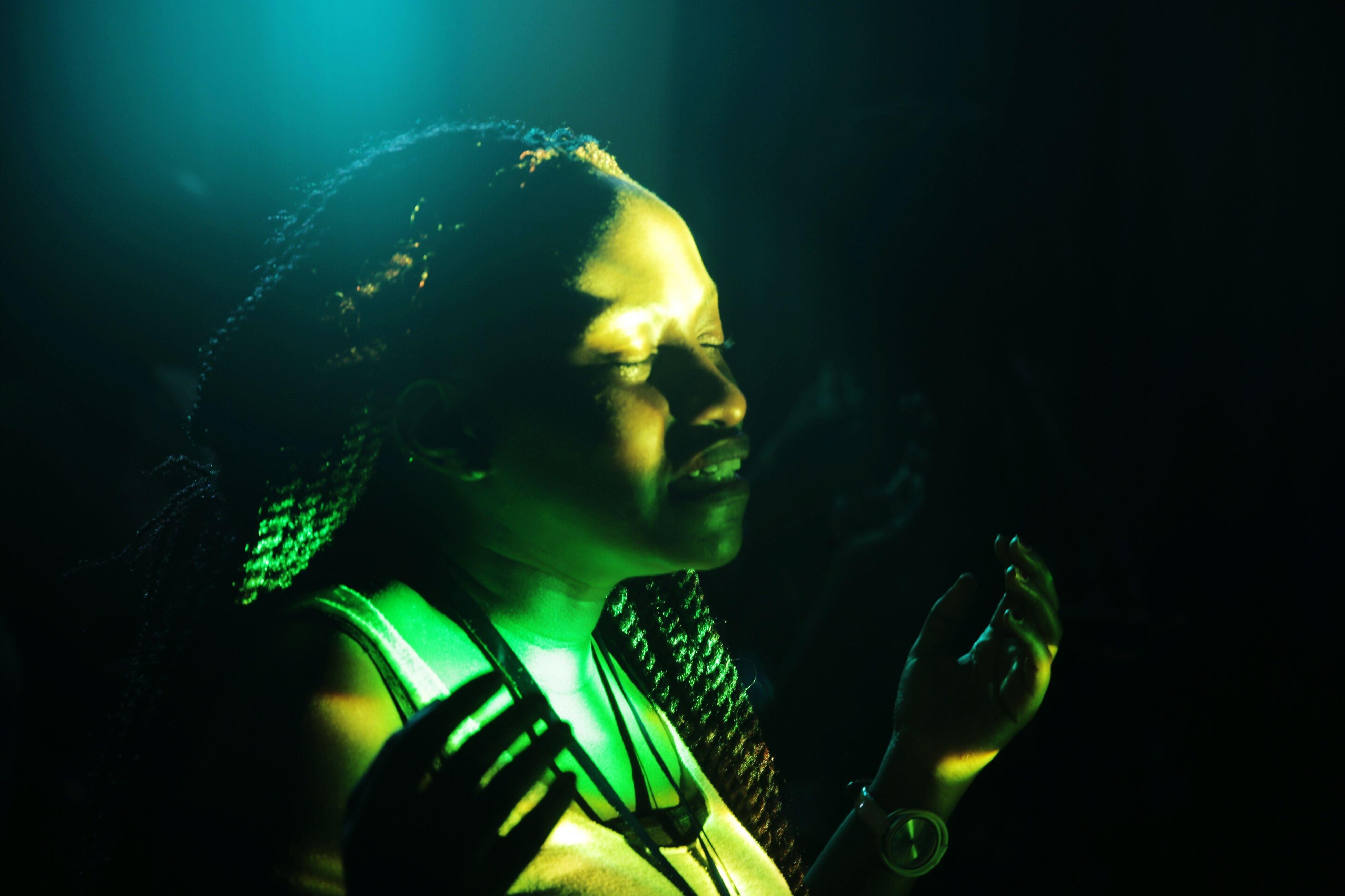 headshot, auto post production filter, black background, green color, studio shot, sunbeam, dark, back lit, long hair, person, multi colored, vibrant color