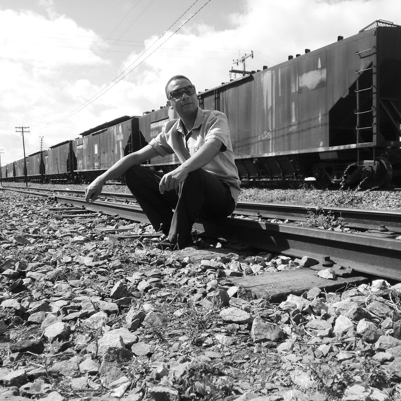 railroad track, one person, sitting, rail transportation, sky, full length, young adult, transportation, real people, outdoors, day, people