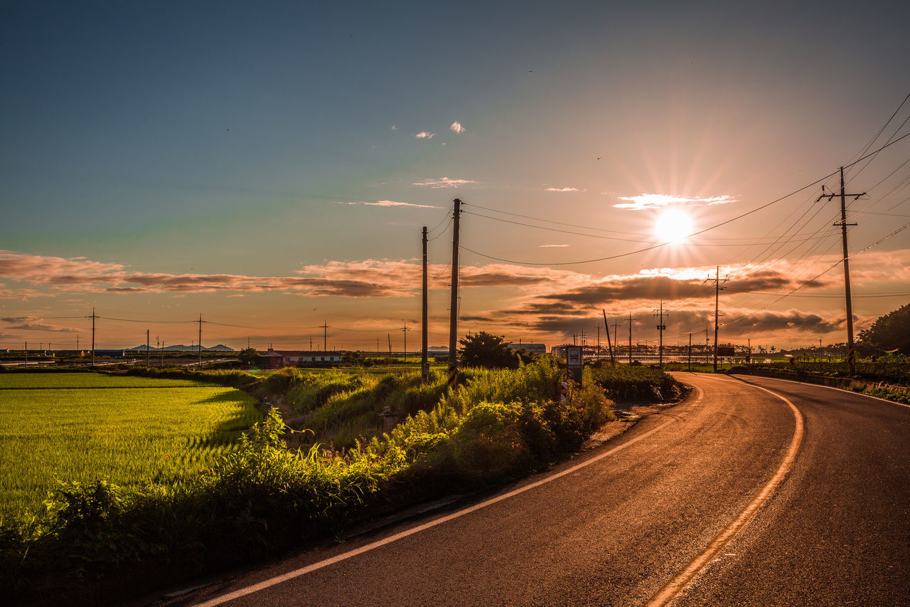 road, sun, no people, sunset, sky, the way forward, nature, electricity pylon, transportation, electricity, scenics, plant, outdoors, sunlight, beauty in nature, fuel and power generation, landscape, tree, day