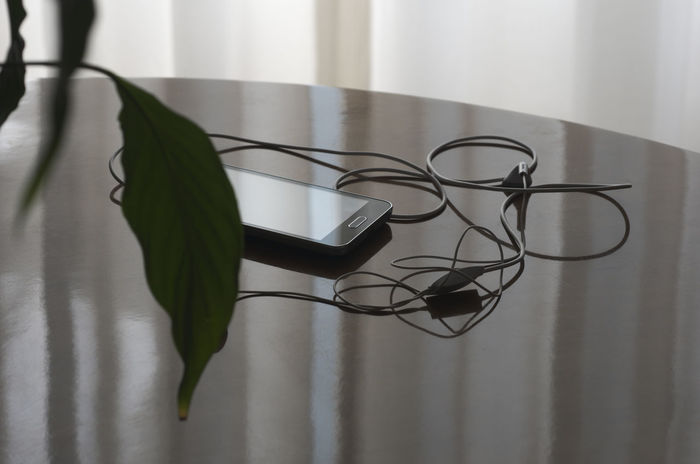 smartphone on table Backlight Cables Cellphone Close-up Communication Connection Earbuds Headphones Indoor Indoors  Interior IPhone Leaf Mobile Music No People Object Phone Plant Smart Phone Smartphone Table Technology