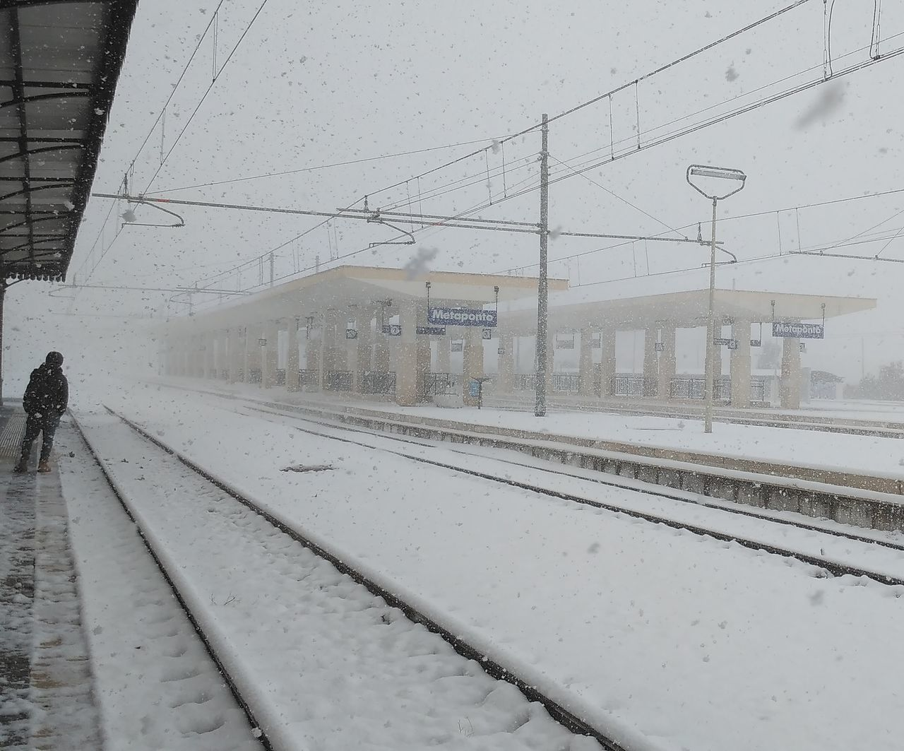 winter, cold temperature, snow, railroad track, transportation, rail transportation, weather, public transportation, railroad station platform, train - vehicle, railroad station, cable, outdoors, snowing, railway track, real people, day, built structure, nature, men, architecture, technology, electricity pylon, one person, people