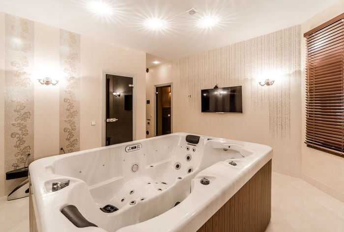 Interior of modern bathroom with jacuzzi Bath Home Hygiene Light Modern Bathroom Bathroom Sink Bathtub Comfortable Domestic Bathroom Domestic Room Illuminated Illumination Indoors  Inside Interior Interior Design Jacuzzi  Modern No People Nobody Relaxation White And Brown
