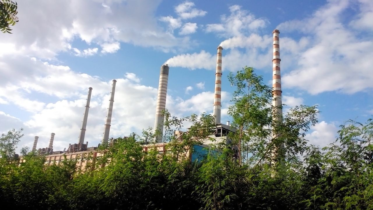 industry, smoke stack, sky, factory, no people, built structure, smoke - physical structure, day, tree, emitting, low angle view, chimney, growth, architecture, outdoors, nature