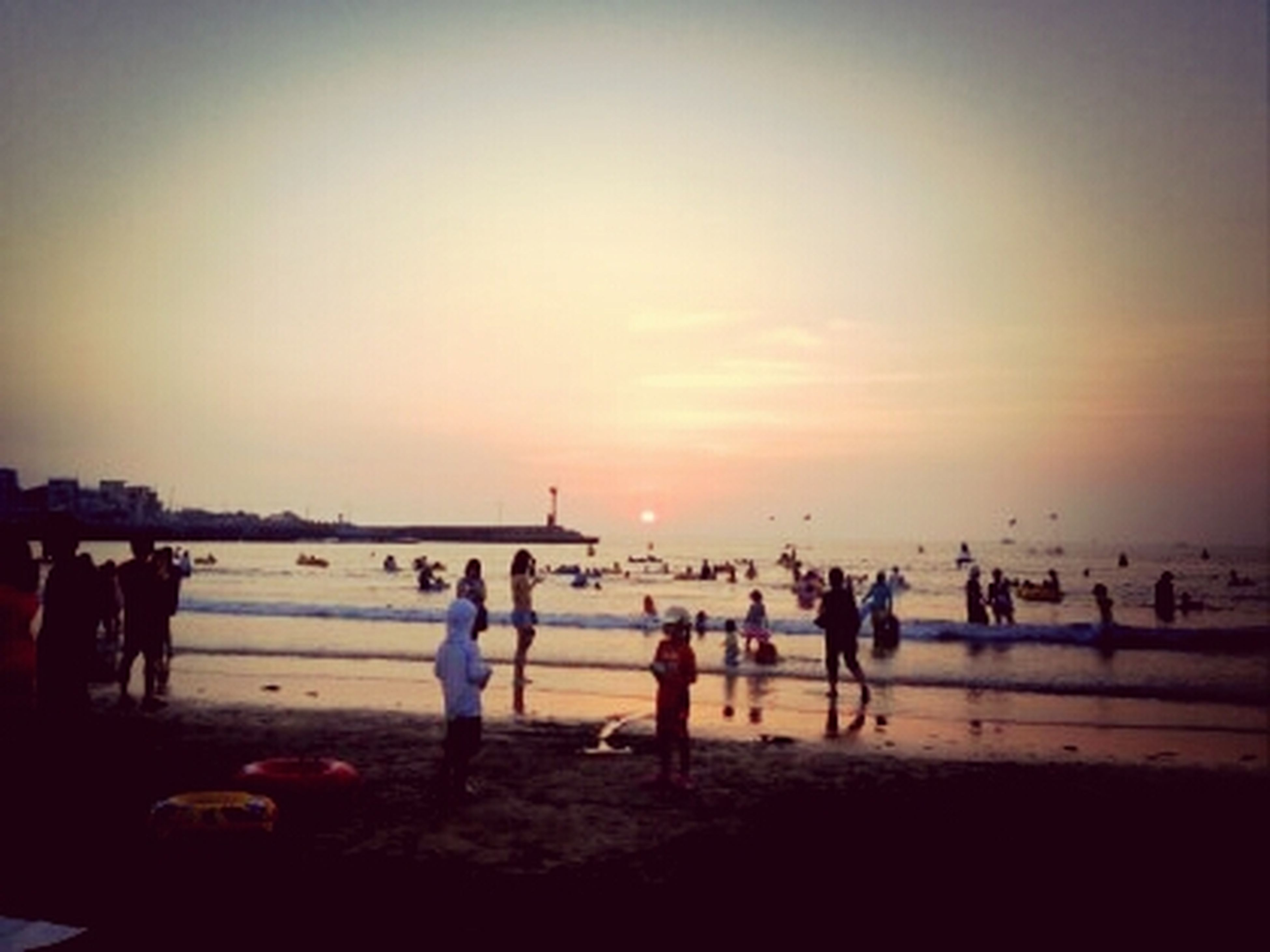 sunset, sea, large group of people, beach, horizon over water, water, silhouette, shore, sky, sun, mixed age range, orange color, scenics, lifestyles, leisure activity, men, beauty in nature, person, copy space