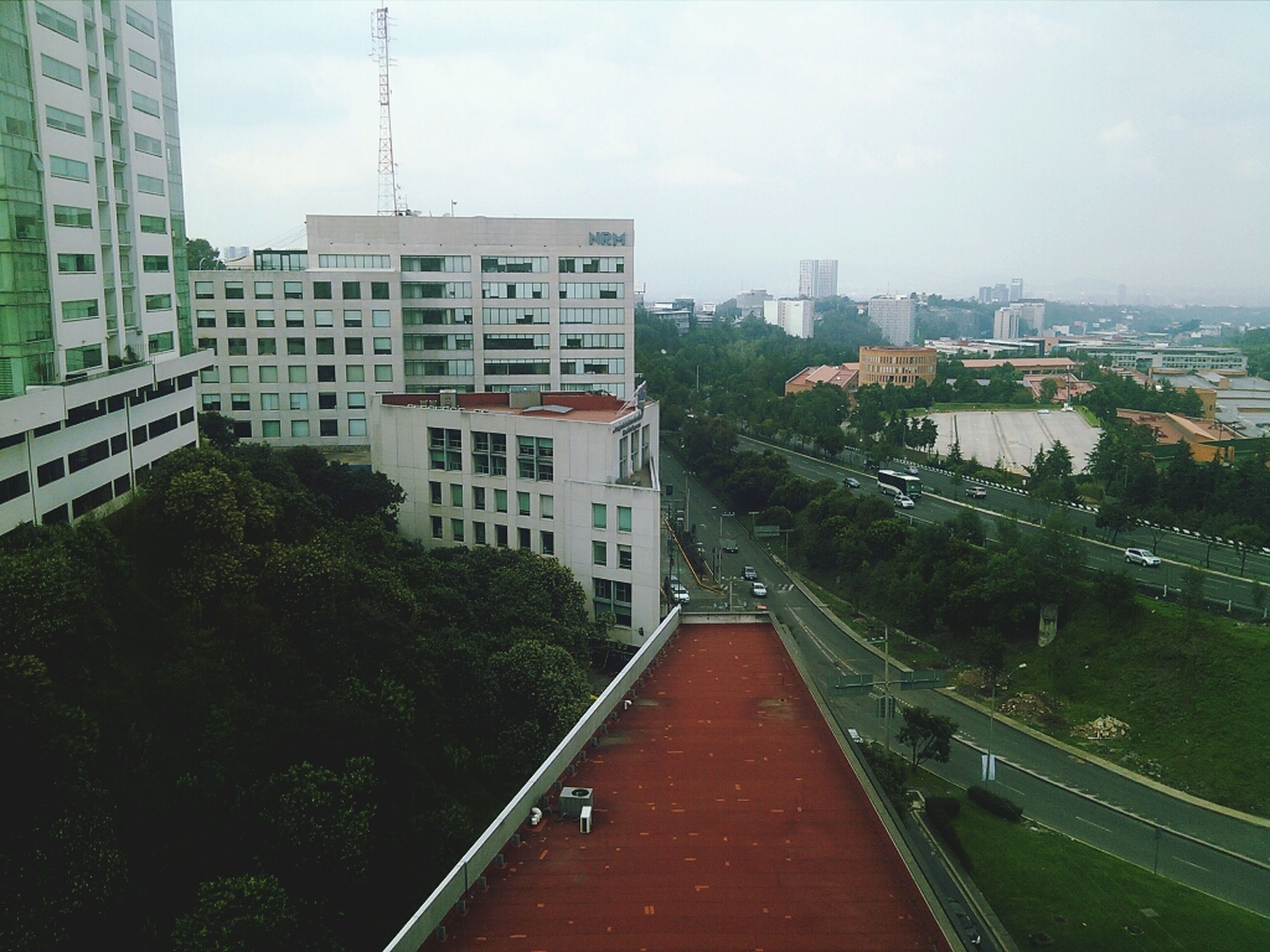 architecture, building exterior, built structure, city, tree, sky, city life, the way forward, residential district, day, office building, outdoors, leading, skyscraper, no people, long, footpath, development, bridge