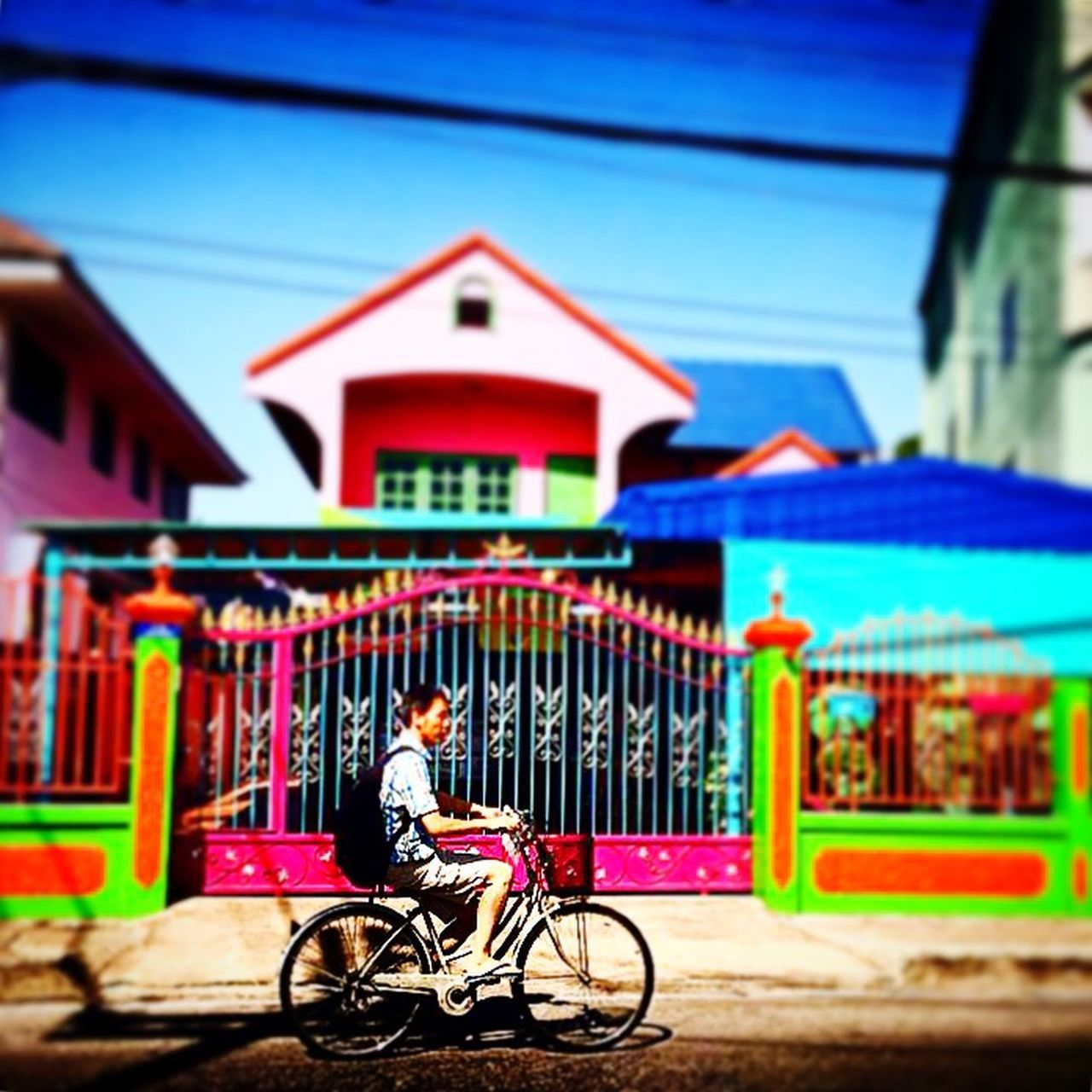 bicycle, architecture, built structure, building exterior, real people, transportation, one person, house, outdoors, mode of transport, cycling, focus on foreground, multi colored, day, land vehicle, full length, lifestyles, headwear, sky, city, people