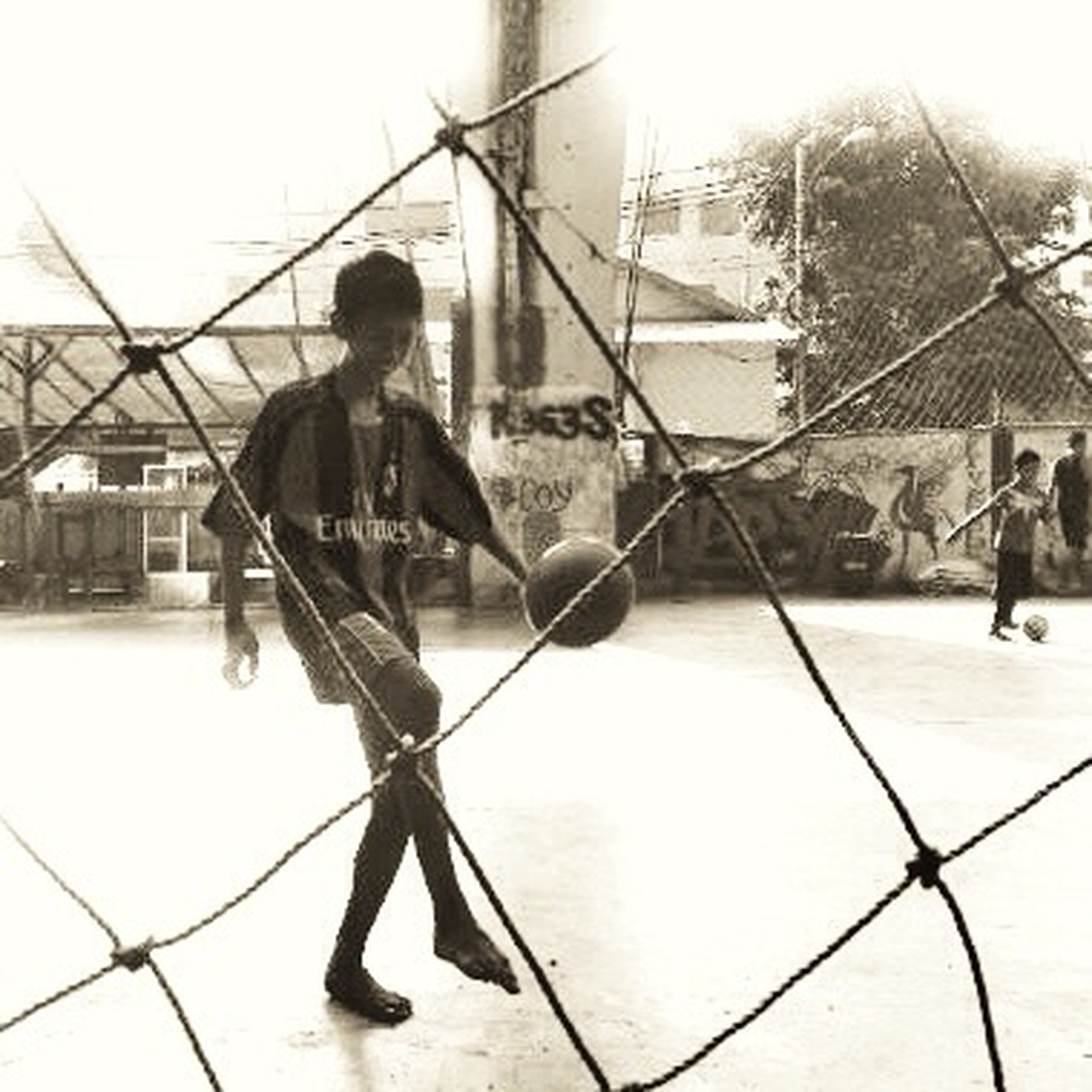lifestyles, leisure activity, full length, childhood, men, chainlink fence, boys, casual clothing, fence, playing, enjoyment, girls, standing, togetherness, protection, fun, sky
