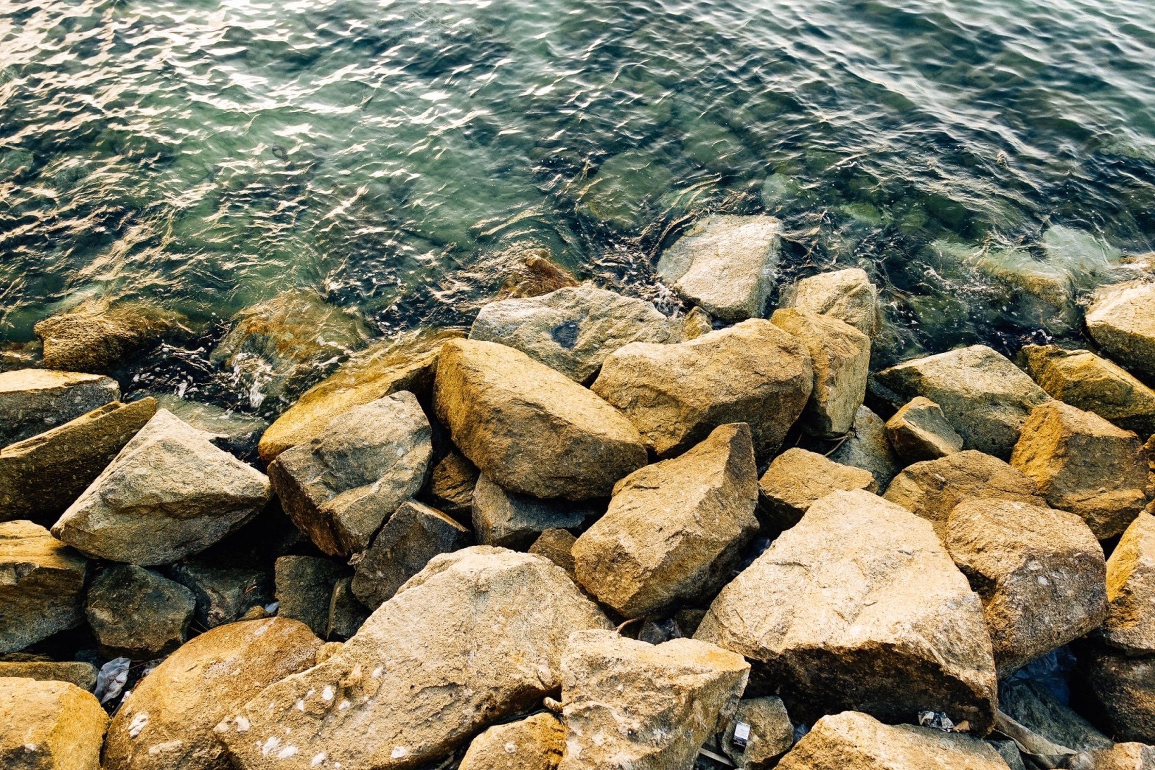 water, rock - object, stone - object, high angle view, nature, pebble, sea, textured, rock, stone, tranquility, day, outdoors, river, shore, beach, beauty in nature, rippled, no people, sunlight
