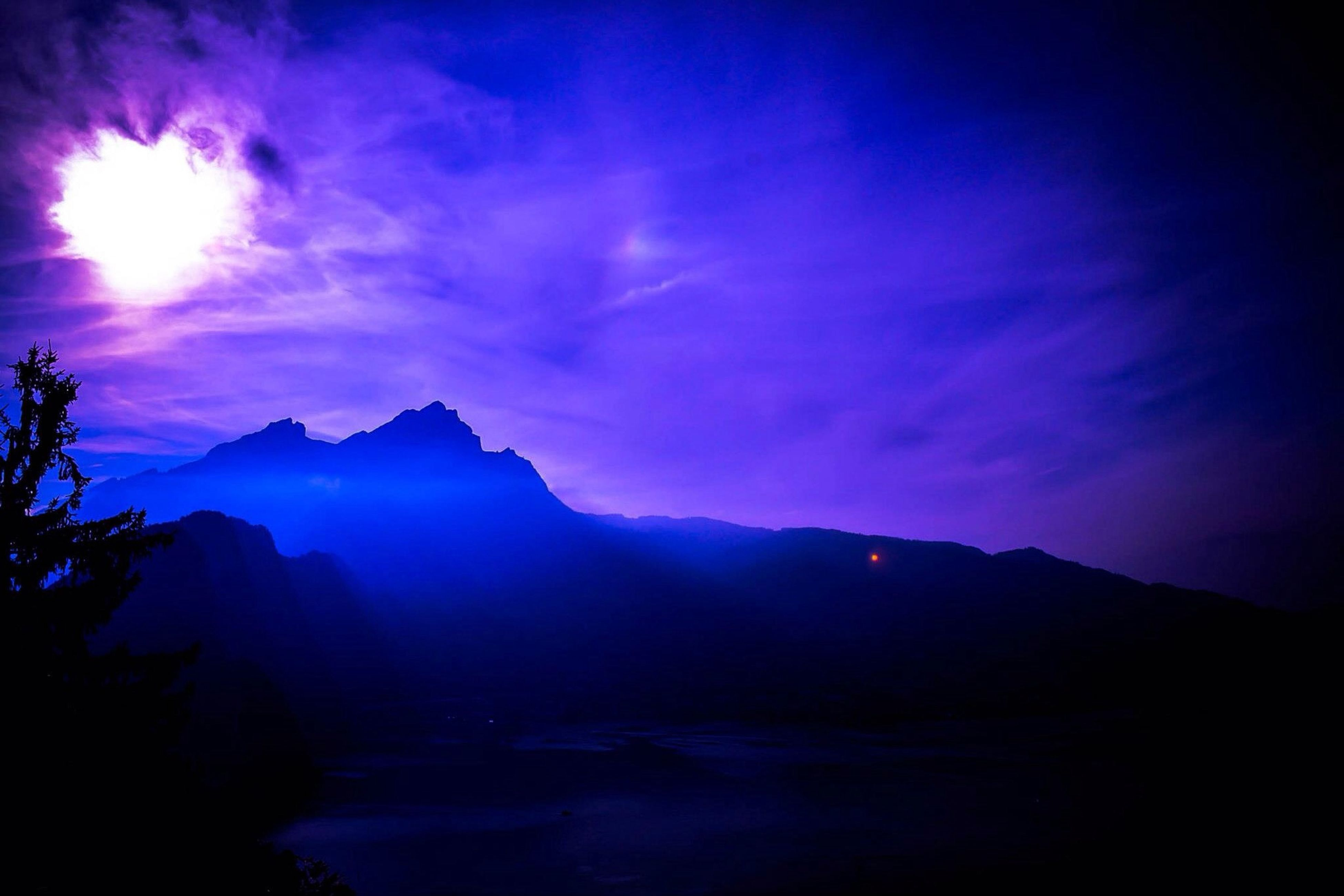blue, beauty in nature, scenics, tranquil scene, sky, tranquility, nature, sunbeam, mountain, idyllic, silhouette, sunlight, lens flare, water, night, outdoors, no people, majestic, tree, cloud - sky