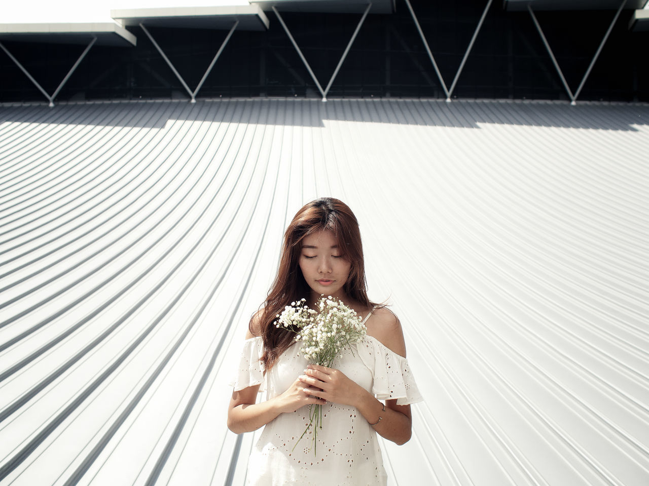 one person, young adult, standing, real people, front view, lifestyles, happiness, day, outdoors, young women, holding, flower, beautiful woman, smiling, bride, adult, people