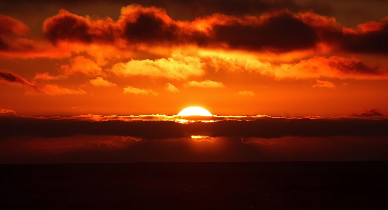 The golden globe of the sun slips softly down through golden fog and clouds into the whispering waves of the ocean. Beauty In Nature Clouds Cloudy Colorful Crimson Darkness Evening Fiery Gold Golden Landscape Nature Orange Passionate Red Romance Romantic Shadows Sky Solar Sun Sunset Twilight Water Yellow