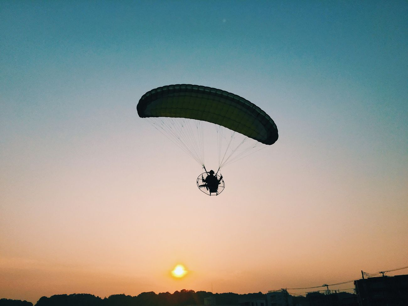 Paraglider flying across the Beach as The Sun Goes Down Magic Moment