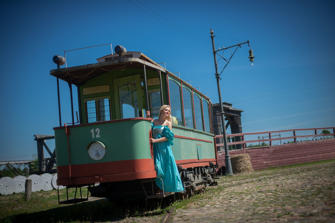 Full Length Of Woman Standing On Old Tram Amidst Field Against Blue Sky