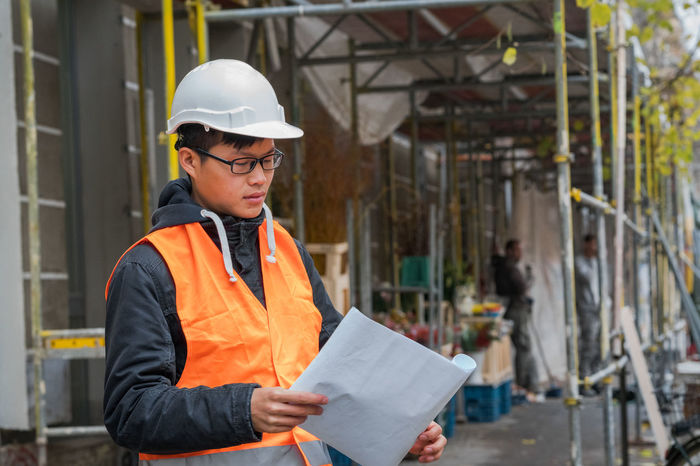 Young Asian engineer wearing protective work wear working on construction site. Outdoors Architecture Asian  Construction Site Growth Improvement Man Plant Safety Hard Hat Work Asian Man Development Engineer Engineering Future Hardhat  Outdoors Person Protection Protective Workwear Real Estate Real People Reflective Clothing Safety Helmet Safety Jacket Young Adult