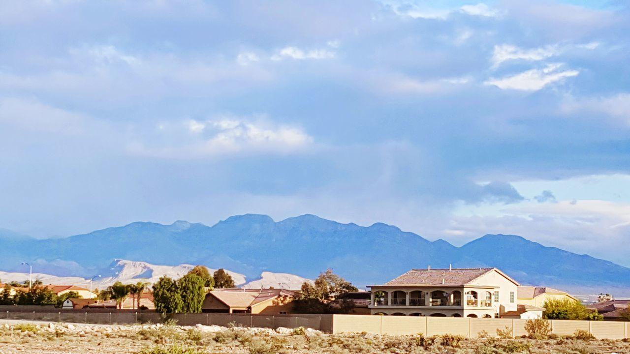 Houses On Mountain Range Against Cloudy Sky