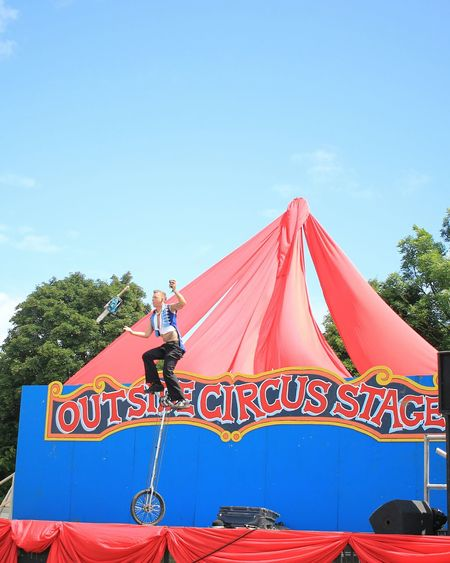 Glastonbury Music Festival Circus Unicycle Juggling Chainsaw Outside Stage at Glastonbury Festival