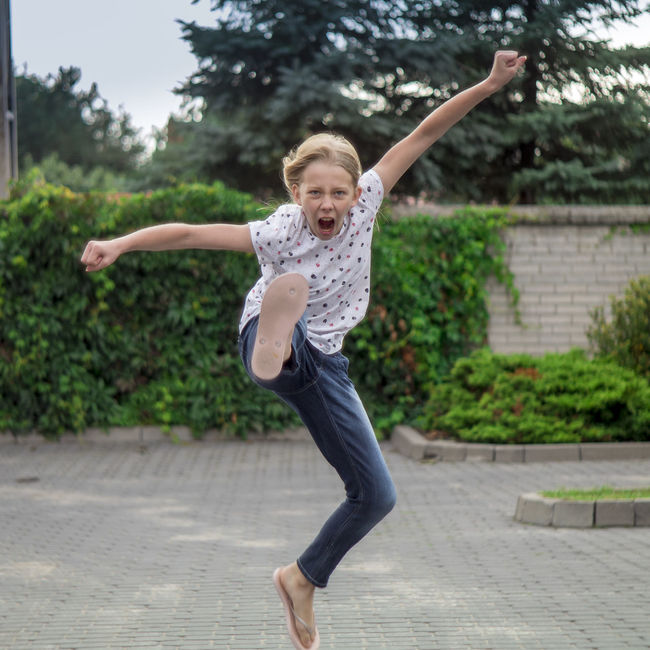 11 years girl shows kungfu kick with leg in the jump , along with a shout . Very realistic and public parking Blond Day Expression Fun Jeans Jump Karate Kick Kid Kungfu  Long Hair Outdoors Panda Parking Person Playing Public Screeming Summer T-shirt Teenager Young Young Women