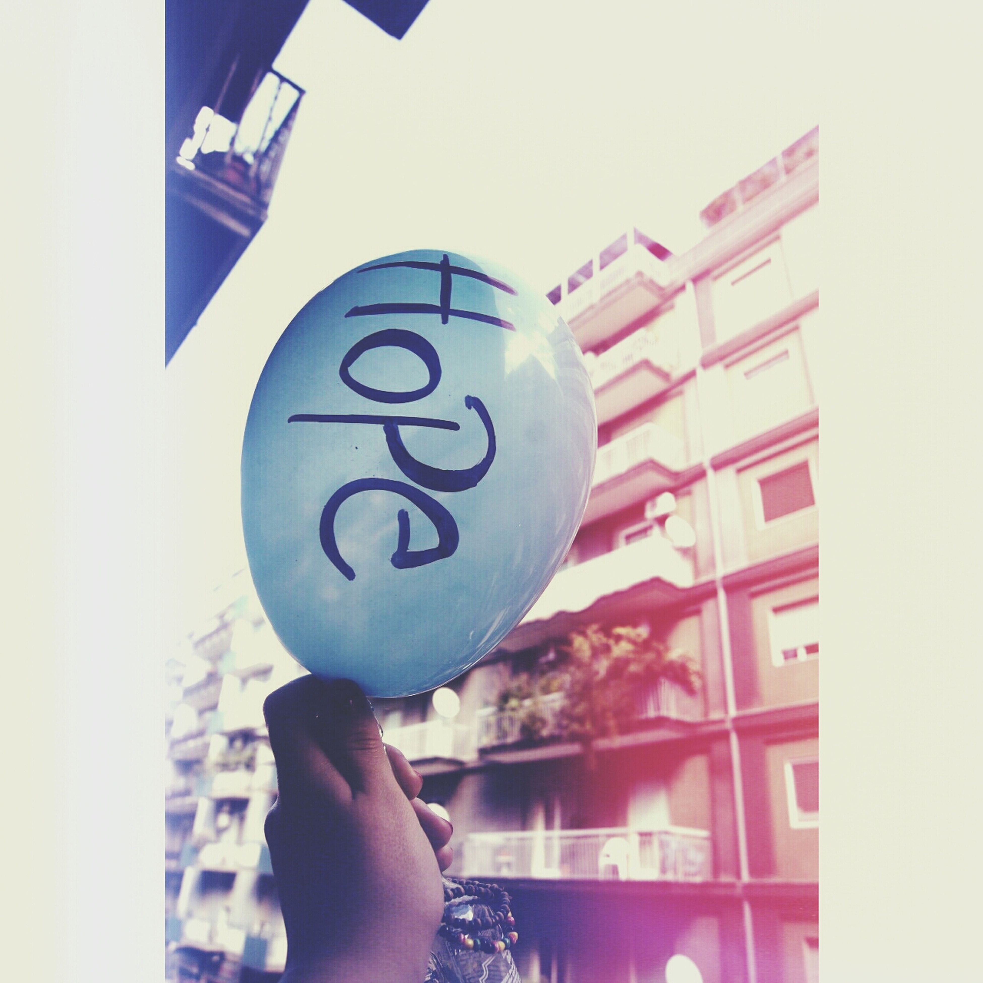 holding, lifestyles, text, communication, leisure activity, architecture, built structure, western script, person, balloon, building exterior, indoors, headshot, childhood, blue, low angle view, wall - building feature, sign