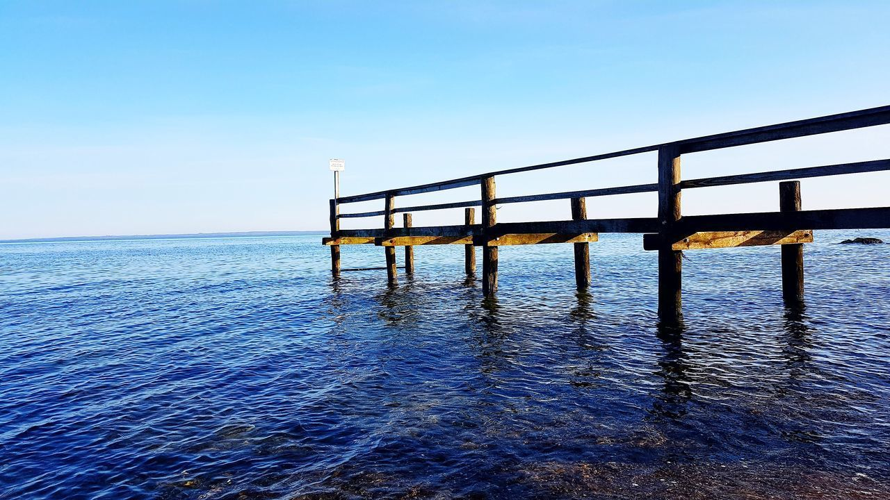 sea, railing, water, nature, outdoors, blue, scenics, day, tranquil scene, horizon over water, no people, tranquility, clear sky, beauty in nature, sky