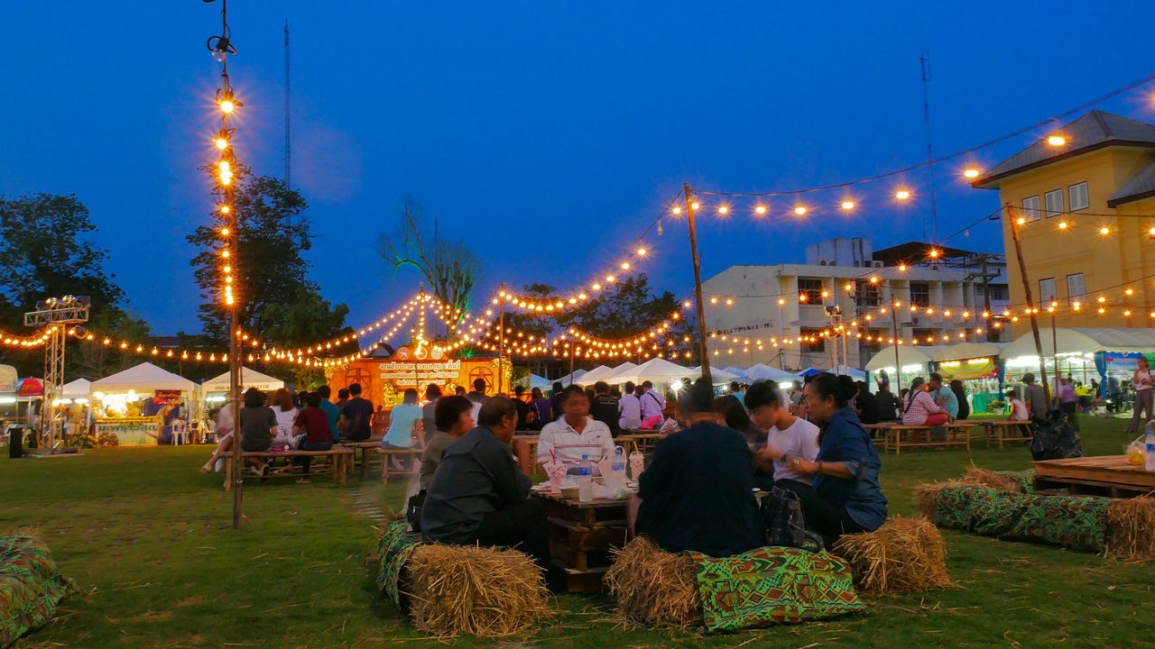 Adult Amusement Park Arts Culture And Entertainment Carousel Celebration Enjoyment Grass Illuminated Large Group Of People Leisure Activity Lighting Equipment Men Night Outdoors People Real People Sitting Sky Tree
