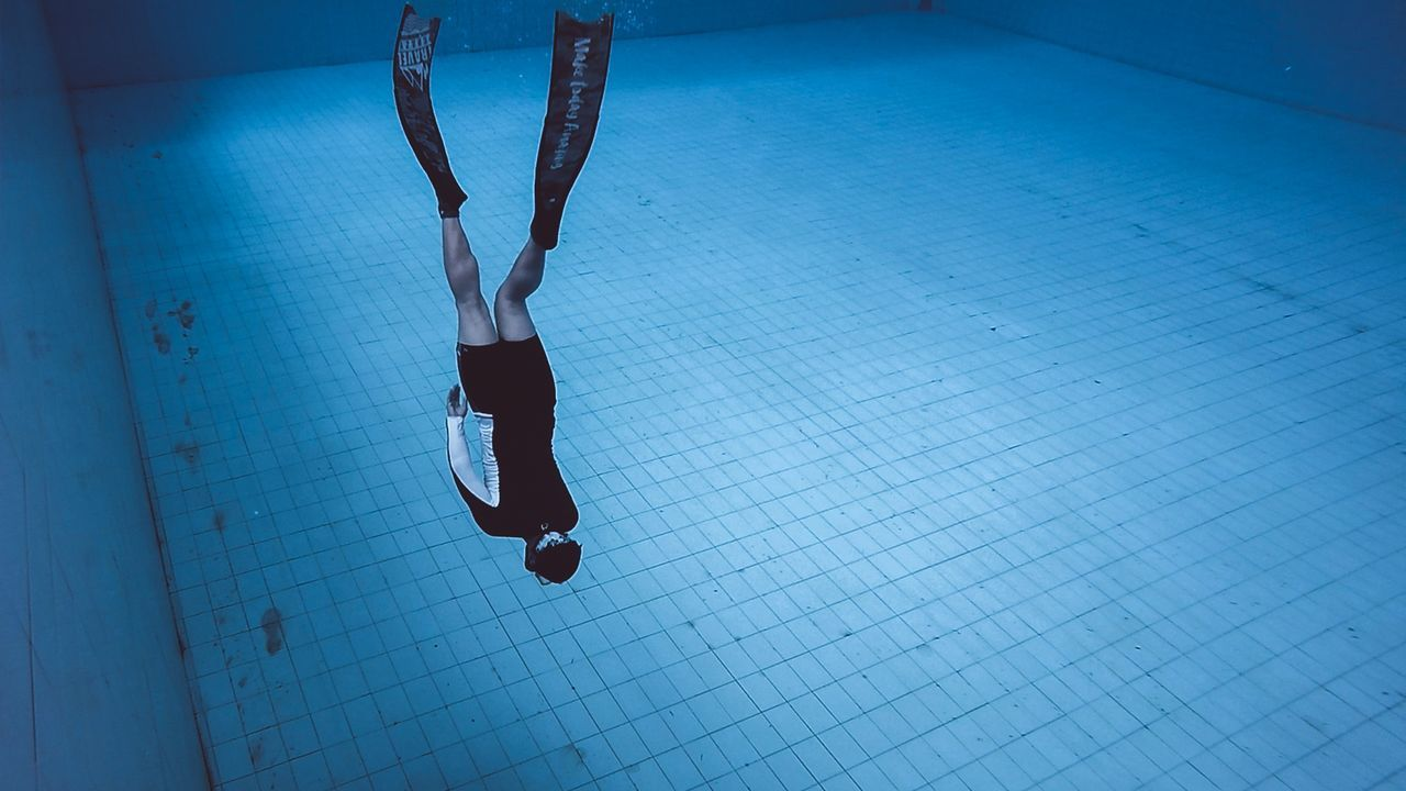 swimming pool, real people, water, exercising, lifestyles, skill, leisure activity, indoors, one person, women, swimming, underwater, full length, sport, day, athlete, people