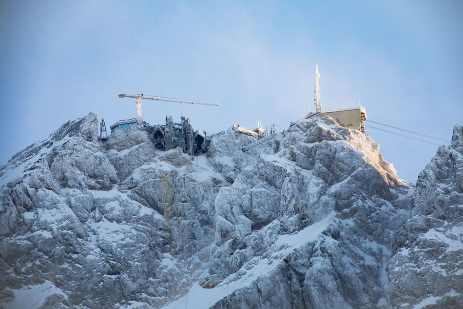 Alps Beauty In Nature Blue Cold Temperature Day Germany Low Angle View Mountain Nature No People Outdoors Overhead Cable Car Scenics Ski Lift Sky Snow Snow Covered Snowcapped Mountain Top Of The Mountain Tranquility Winter Winter Zugspitze