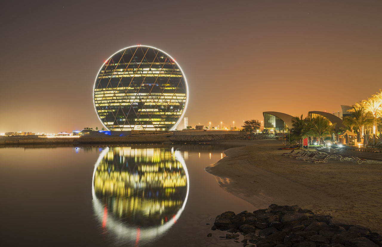 water, reflection, architecture, built structure, night, building exterior, illuminated, sky, travel destinations, sunset, no people, nature, beach, outdoors, ferris wheel, city, clear sky, beauty in nature, cityscape