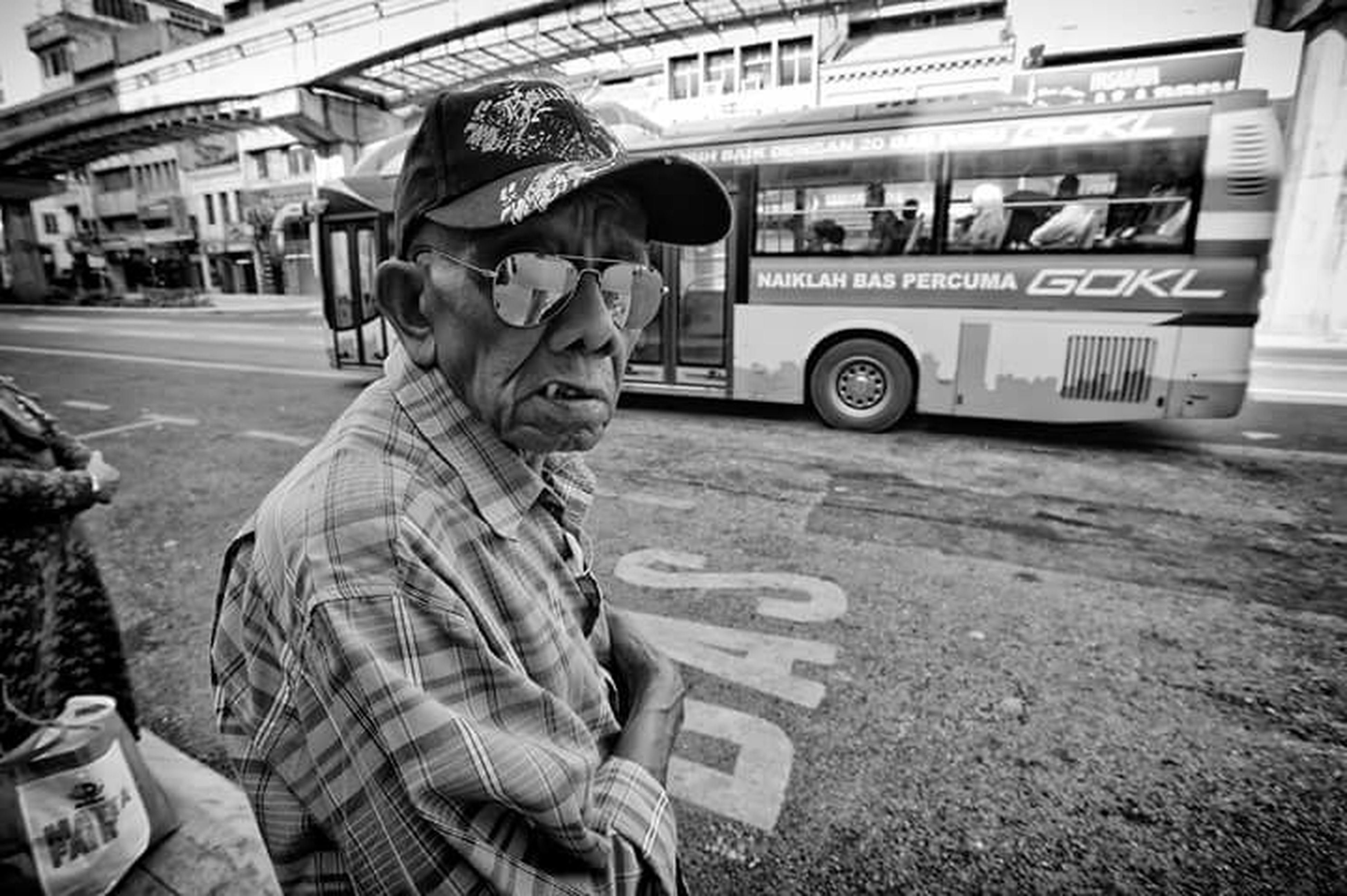 transportation, land vehicle, mode of transport, street, car, road, casual clothing, lifestyles, travel, leisure activity, city, public transportation, sleeping, full length, city life, holding, person, homelessness, outdoors, day, focus on foreground