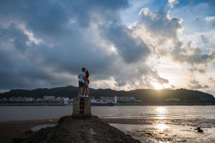 Young Adult Friendship Real People Day Outdoors Mid-air Full Length Water Two People Sky Cloud - Sky Togetherness Love Heterosexual Couple Tranquility People Beach Standing Nature Sea Scenics Men Tranquil Scene Beauty In Nature Rear View