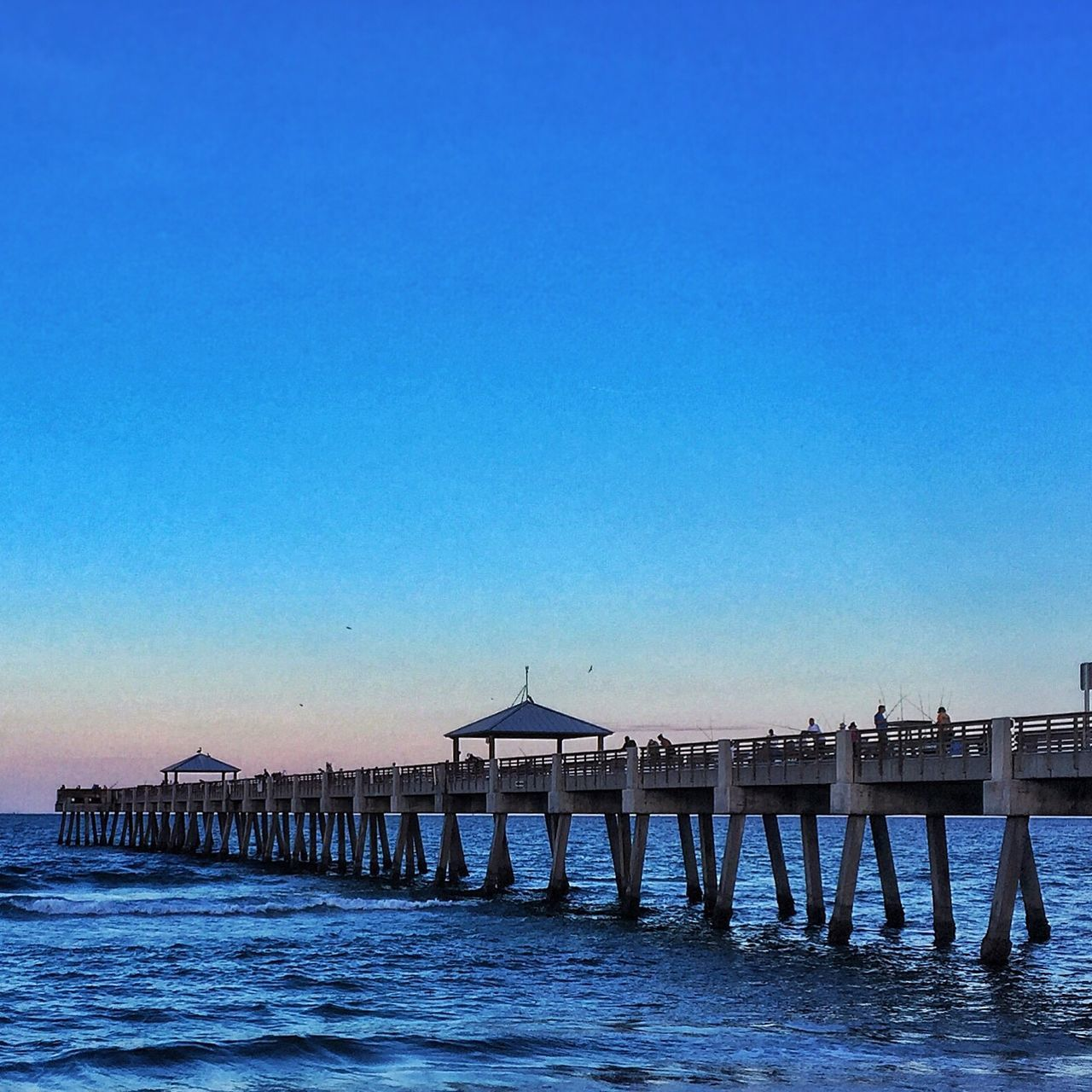 architecture, built structure, water, blue, pier, copy space, sea, outdoors, connection, clear sky, waterfront, no people, beach, building exterior, day, nature, sky, scenics, beauty in nature