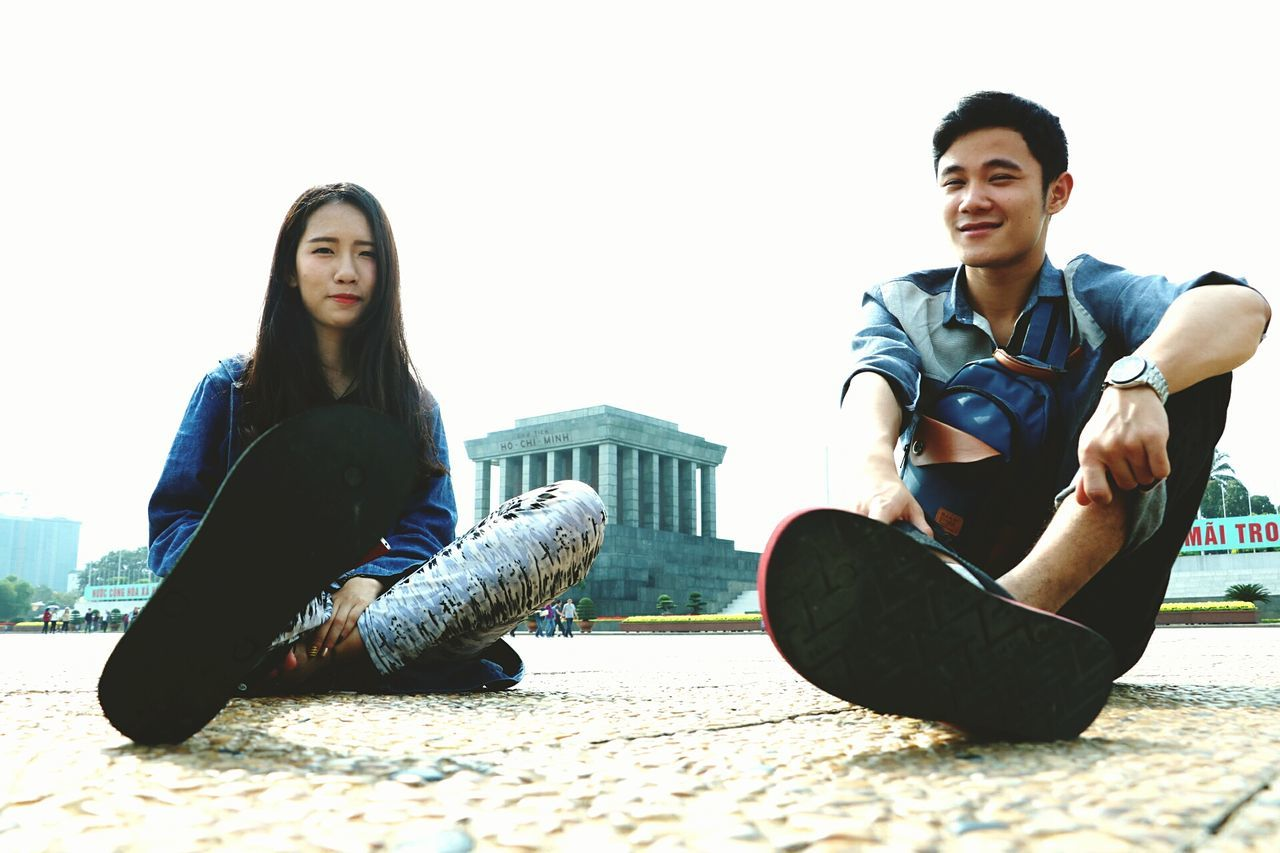 two people, full length, young adult, casual clothing, togetherness, sitting, young women, young men, real people, lifestyles, leisure activity, front view, day, looking at camera, relaxation, friendship, happiness, portrait, clear sky, bonding, smiling, outdoors, beautiful woman, people