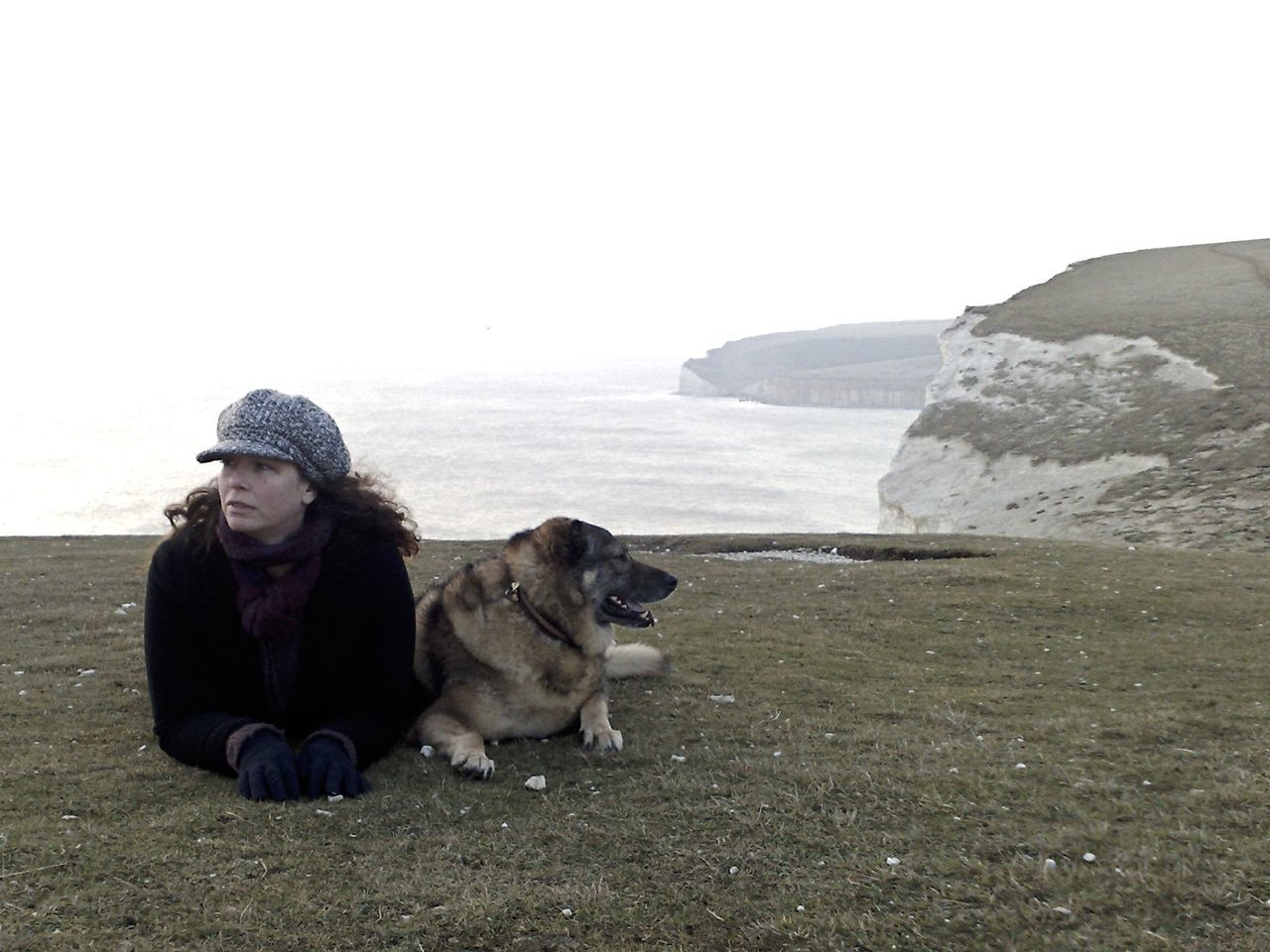 A Hard Day's Walk Animal Themes Beauty In Nature Clear Sky Cliff Day Dog Domestic Animals English Channel Full Length Mammal Nature One Animal One Person Outdoors People Pets Real People Sea Sea And Sky Seven Sisters Seven Sisters Cliffs Sitting Sky Warm Clothing