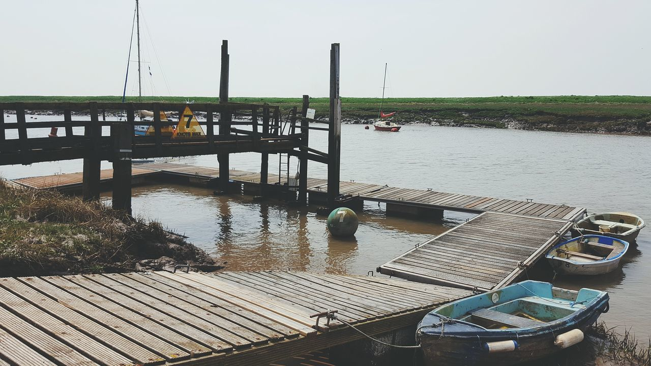Boats Moored At Pier In Lake