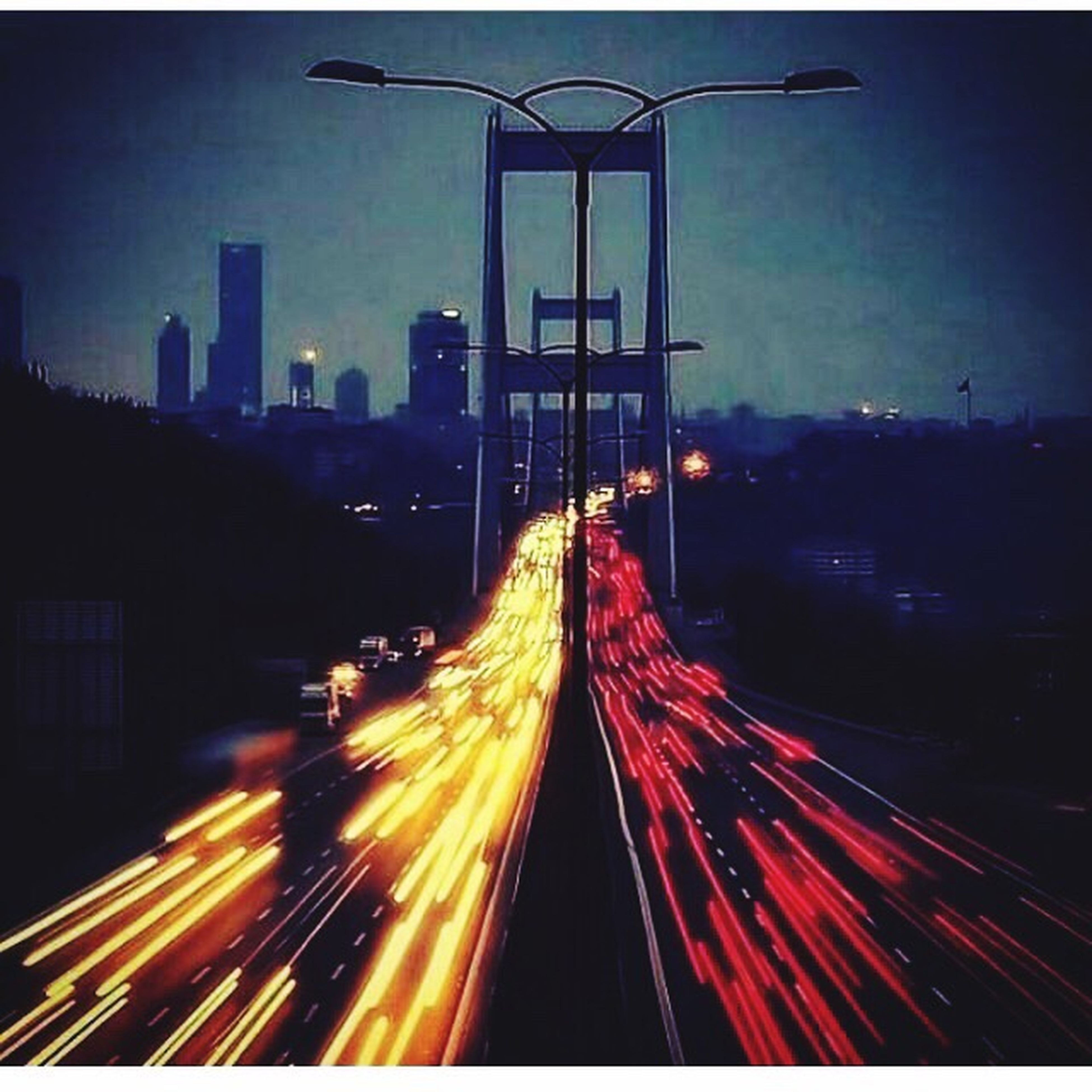illuminated, long exposure, light trail, night, transportation, motion, speed, blurred motion, city, architecture, traffic, red, built structure, on the move, road, city life, the way forward, sky, building exterior, high angle view