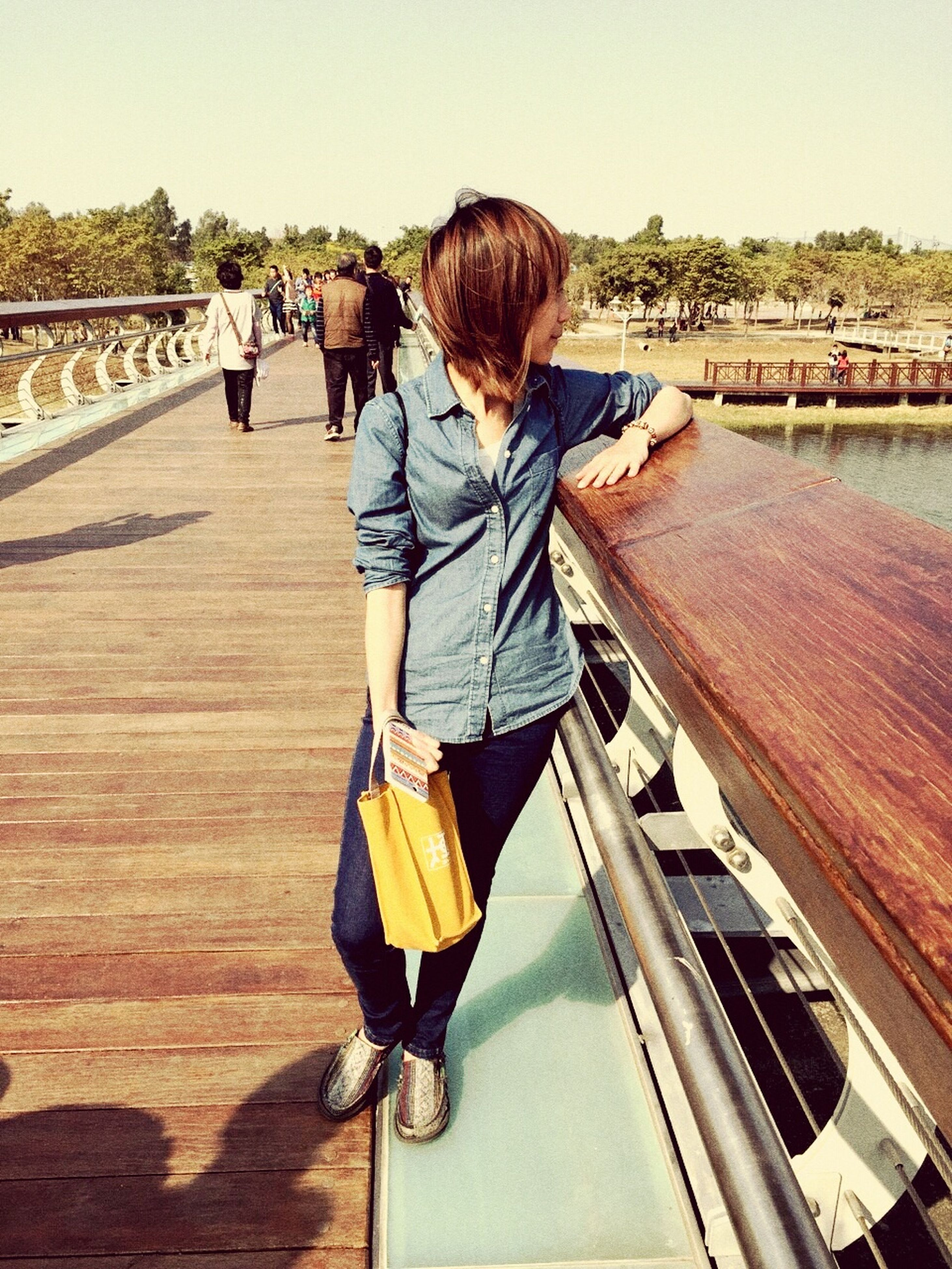 rear view, full length, lifestyles, railing, leisure activity, walking, transportation, the way forward, men, person, casual clothing, bridge - man made structure, connection, water, footbridge, built structure, standing