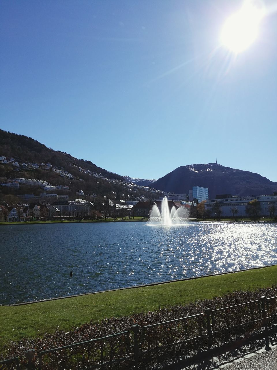water, mountain, nature, beauty in nature, built structure, scenics, sunlight, architecture, tranquil scene, outdoors, day, lake, no people, sun, mountain range, tranquility, sky, clear sky, building exterior, travel destinations, landscape, spraying, grass