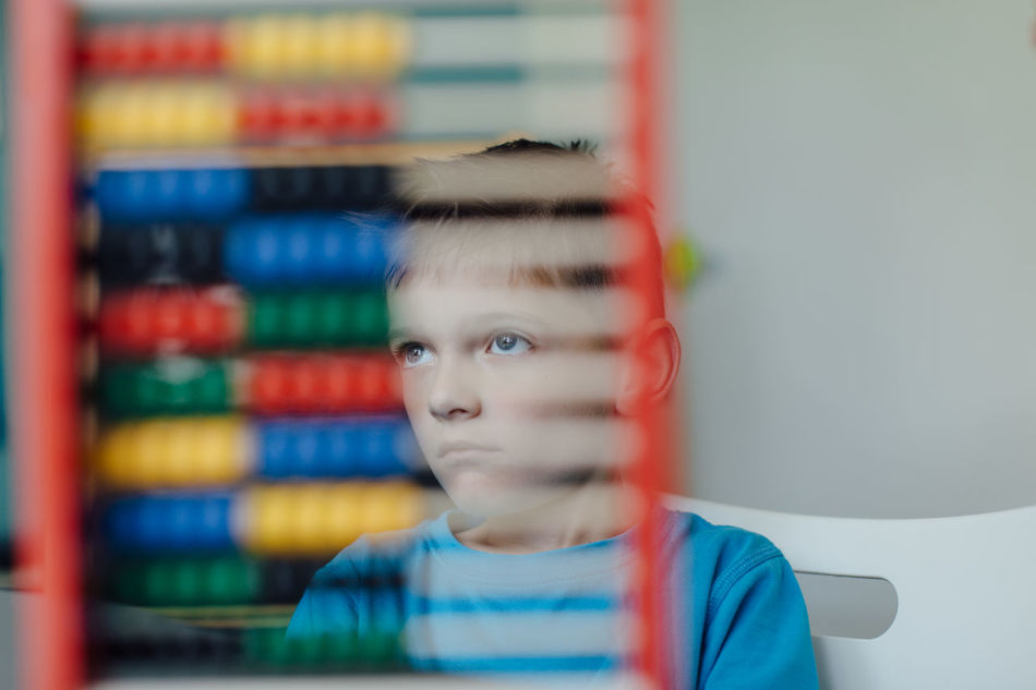 Absent minded schoolboy gazing away through an abacus Abacus Assignment Boy Caucasian Child Counting Critical Home Homeschooling Homework Independent  Kid Learn Learning Mathematics Maths Project Room School Schoolboy Schoolchild Solitary Student Thinking Young