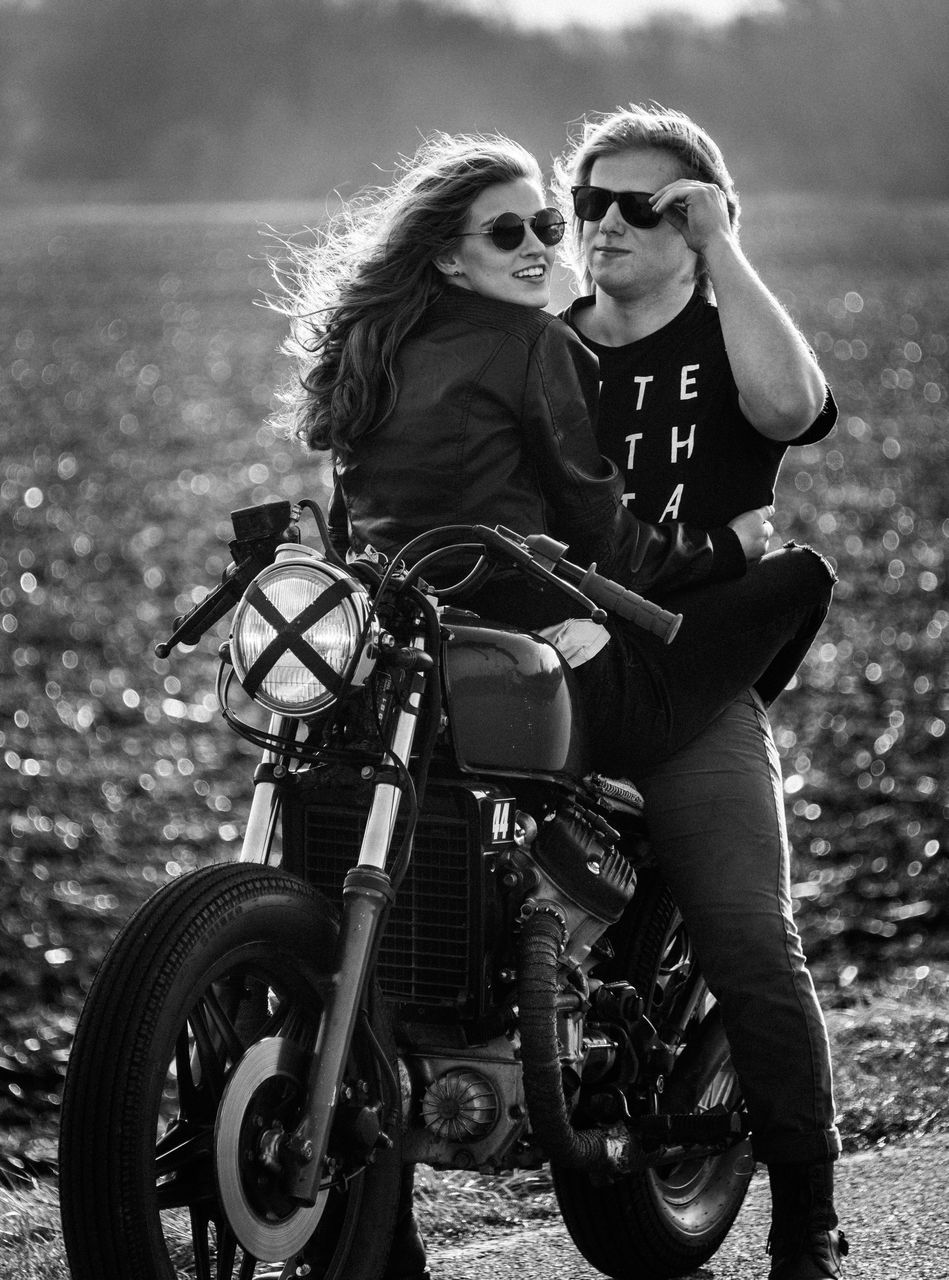 two people, real people, motorcycle, togetherness, bonding, young women, young adult, love, outdoors, lifestyles, field, day, riding, standing, portrait, full length, women, men, headwear, friendship, blond hair, adult, people