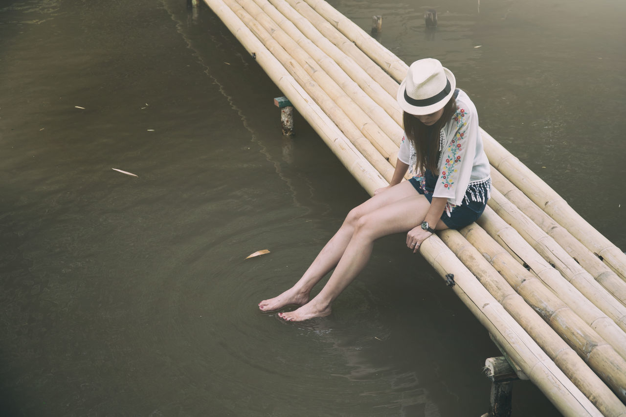 Alone girl swing legs over water. Bamboo - Material Bridge Bridge - Man Made Structure Day Girl High Angle View Human Hand Lake Leisure Activity Lifestyles Nature Nautical Vessel One Person Outdoors Raft Real People Relax Relaxation Swimming Swing Swing Legs Water Water Reflections Waterfront Woman