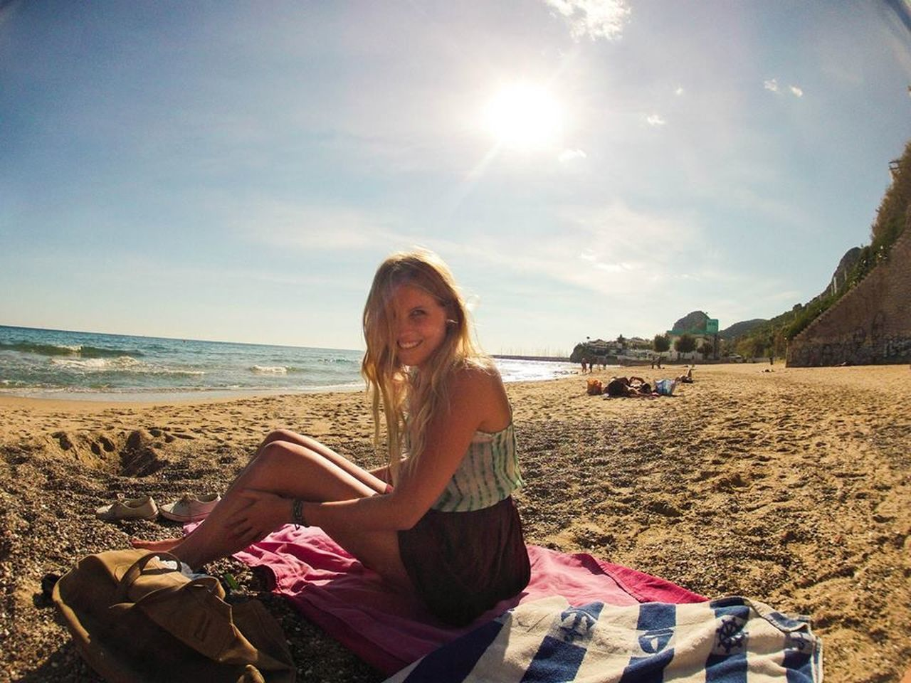 beach, nature, sitting, looking at camera, one person, sunlight, sky, vacations, smiling, sea, young adult, portrait, leisure activity, sand, young women, water, day, real people, outdoors, casual clothing, beautiful woman, beauty in nature, happiness, full length, lifestyles, relaxation, blond hair, horizon over water, adult, adults only, people