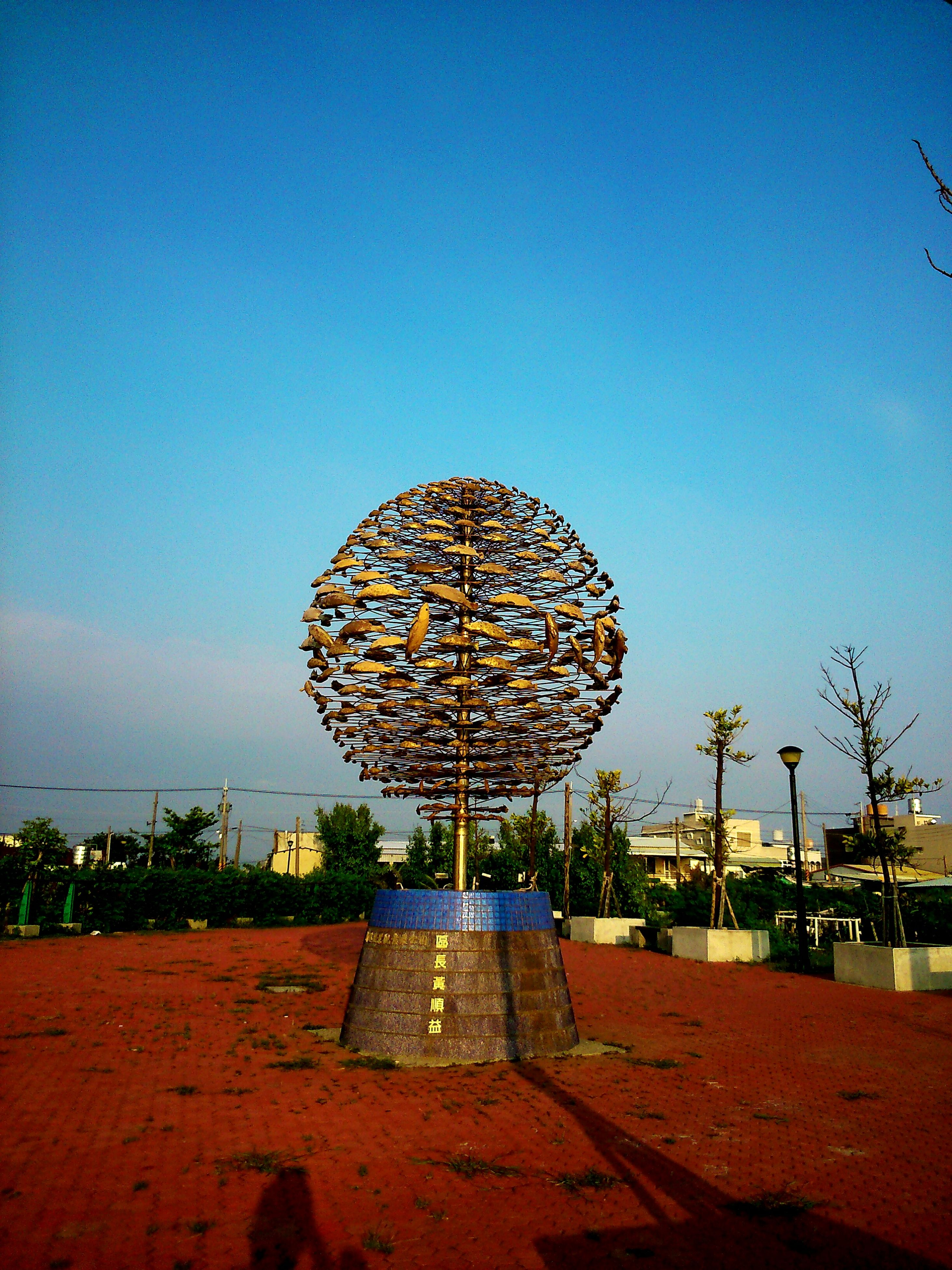 clear sky, blue, copy space, tree, lighting equipment, sky, outdoors, circle, built structure, no people, sunlight, tranquility, street light, nature, illuminated, day, ferris wheel, low angle view, arts culture and entertainment, tranquil scene