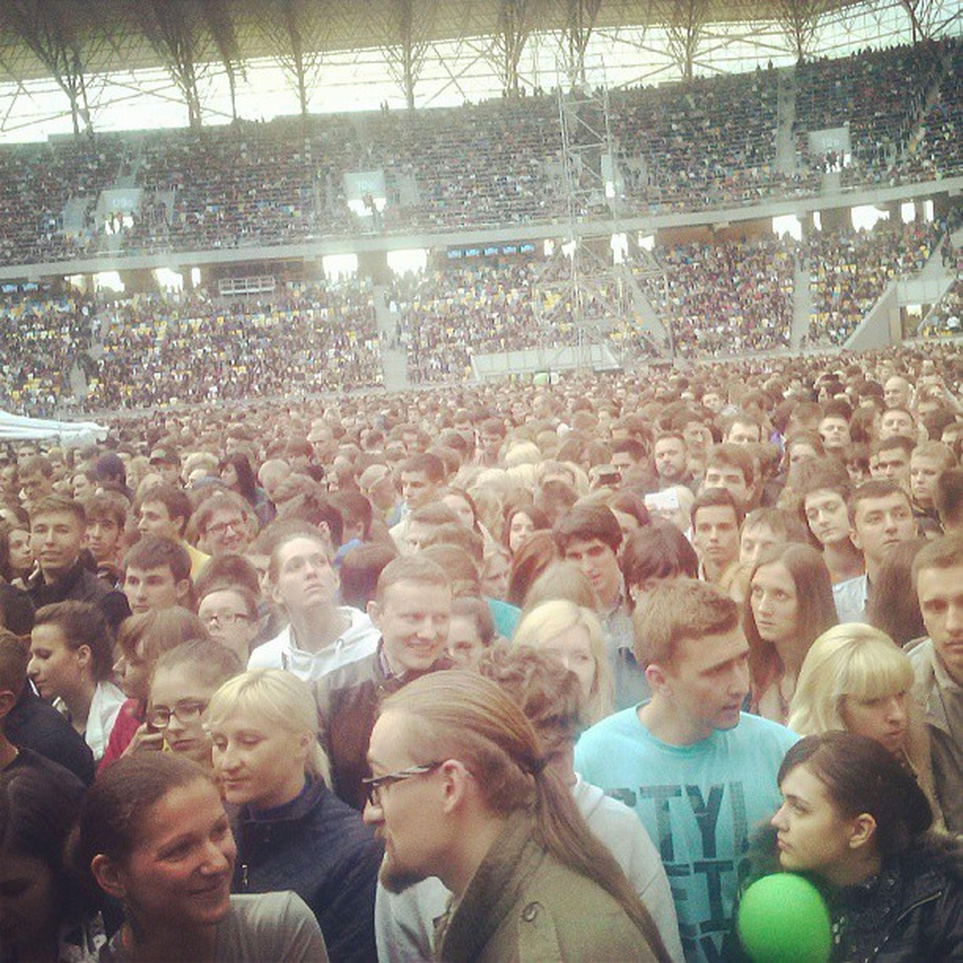 large group of people, lifestyles, crowd, leisure activity, togetherness, men, person, enjoyment, fun, illuminated, celebration, crowded, spectator, event, standing, mixed age range, high angle view, enjoying