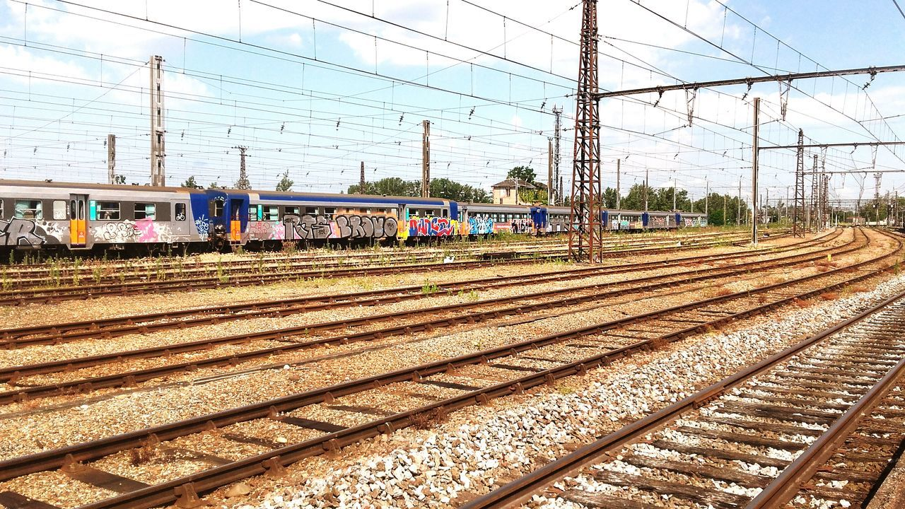 railroad track, rail transportation, cable, transportation, power line, electricity pylon, day, power supply, electricity, public transportation, railroad station, outdoors, no people, sky