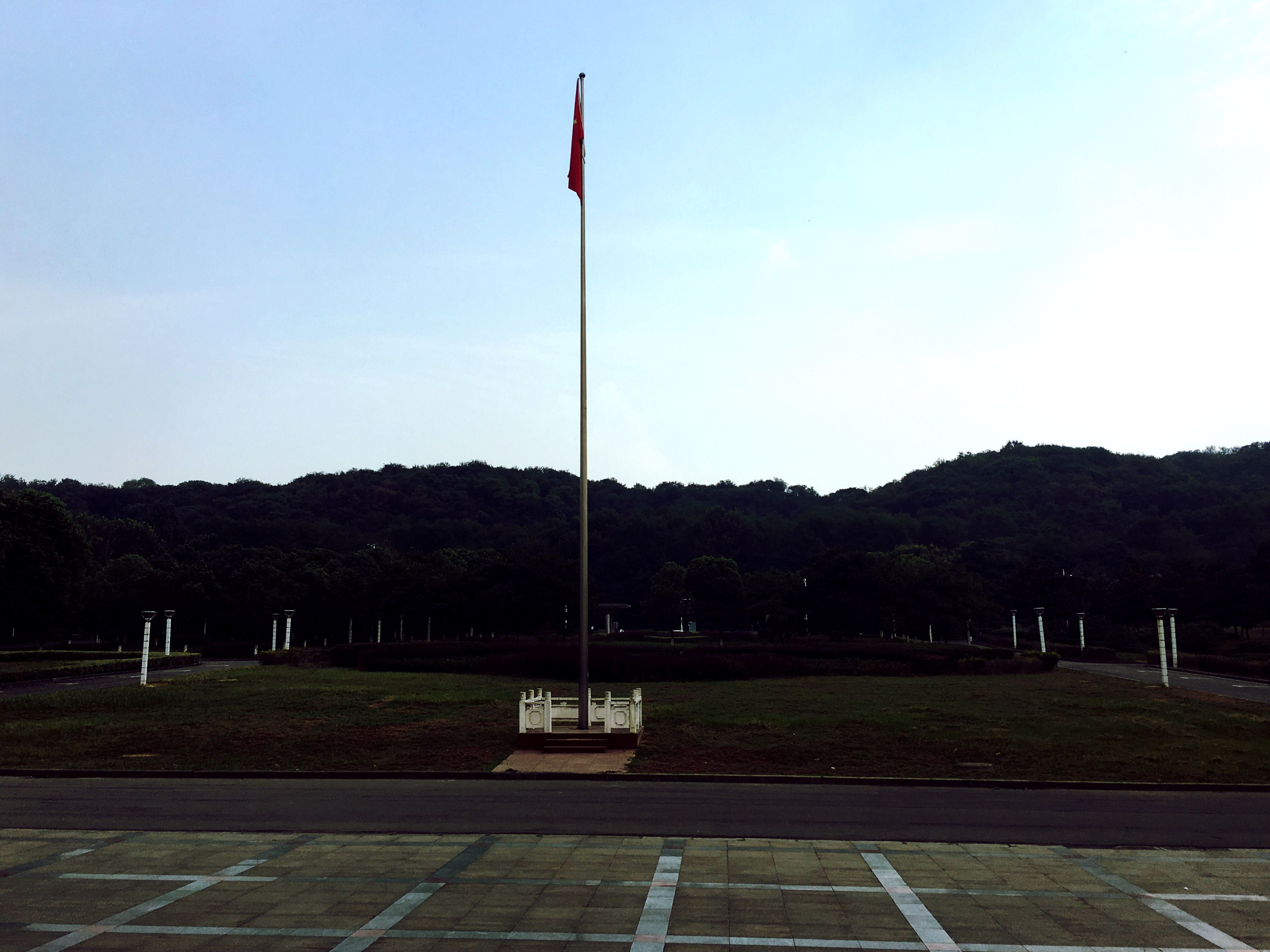 flag, tranquility, park - man made space, clear sky, pole, tranquil scene, national flag, identity, outdoors, scenics, sky, mountain, no people, non-urban scene, red, beauty in nature, hobbies, solitude